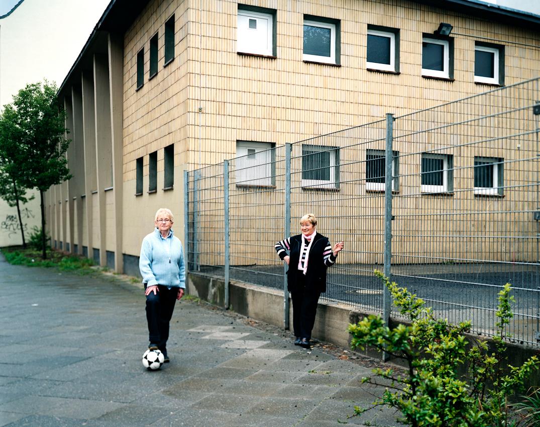 """""""Pionierinnen des deutschen Frauenfussball""""  ist ein Buch und - Ausstellungsprojekt von Gunther Bauer zur Frauenfussball-Weltmeisterschaft 2011 für das Persönlichkeiten, die in einem ganz besonderen Zusammenhang zum Frauenfussball stehen oder standen, portraitiert werden. Anne Droste (links) und Renate Bress (rechts) waren Gründungsmitgliederinnen des Ausnahmeteams Fortuna Dortmund, das ungeachtet des Damenfussballverbots durch den DFB 1955 gegründet wurde.  Die 73 jährigen Pionierinnen der ersten Stunde treffen sich am 07.05.2010 zum Kick auf der gegenüberliegenden Strassenseite von Frau Drostes Elternwohnung, dem Treffpunkt der Dortmunder Fussballdamen. Von klein an spielten sie mit Frau Drostes Bruder und seinen Freunden auf der Strasse im Dortmunder Norden """"von Kellerloch zu Kellerloch""""  Fussball. 1956 waren sie auch als Nationalspielerinnen beim ersten inoffiziellen Damen-Länderspiel in Essen vor 18.000 Zuschauern gegen Holland dabei. Trotz des Verbots des Damenfussball durch den DFB brachten sie es auf über 100 Länderspiele fur die deutsche Damen-Nationalmannschaft."""