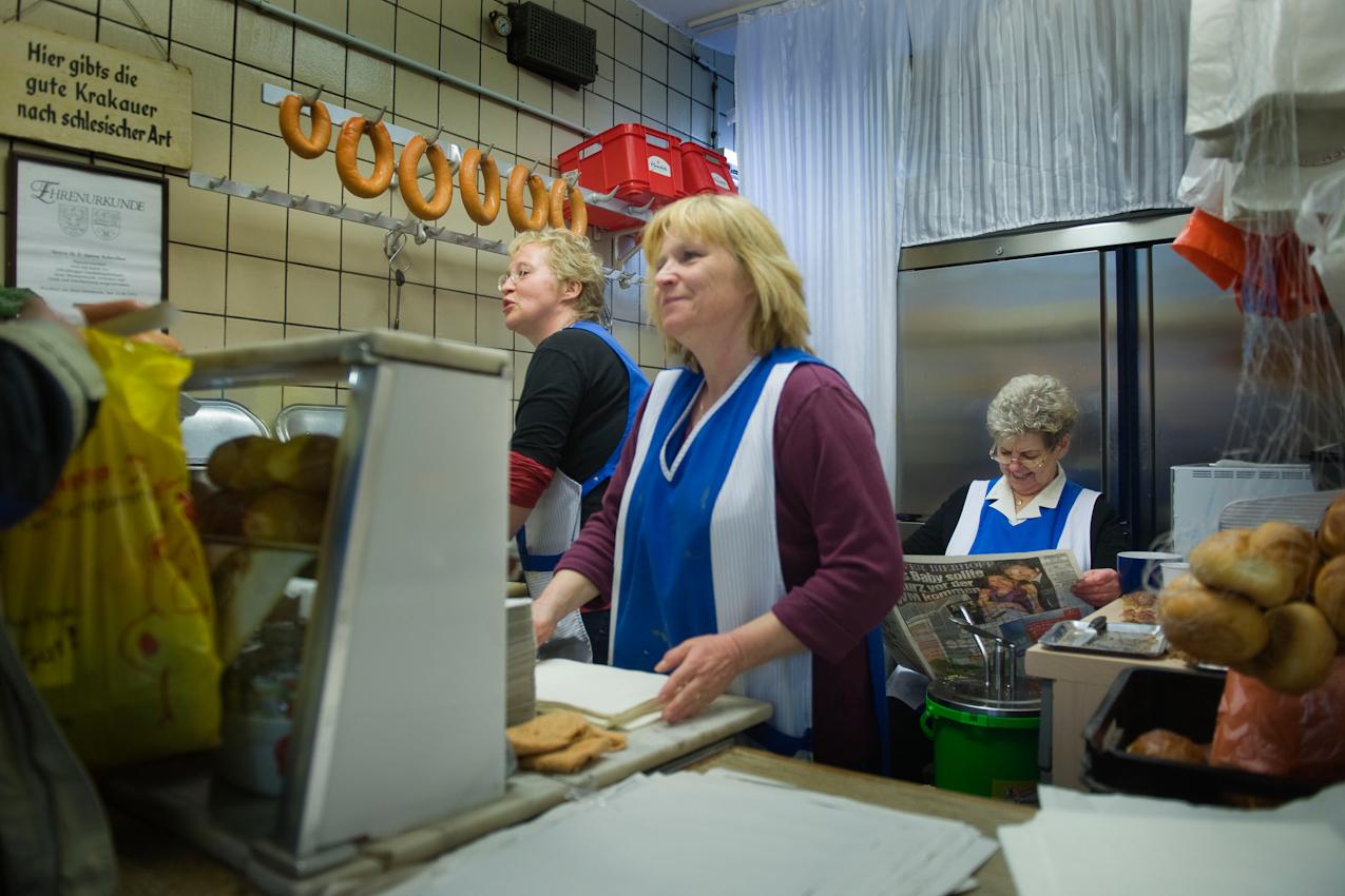 """Ilse Schreiber (rechts) macht eine kleine Kaffeepause in ihrem Wurst Verkaufsstand in der Kleinmarkthalle in der Innenstadt von Frankfurt am Main am Freitag, 07.05.2010. Frau Schreiber arbeitet hier seit 1979 und verkauft hauptsächlich """"the big three"""", d.h. warme Fleischwurst, Rindswurst und Krakauer, mit und ohne Haut. Zur Pause gibt es bei Frau Schreiber eine große Tasse Kaffee, ein belegtes Brötchen und jeden Tag eine andere Zeitung. Links von ihr stehen ihre beiden Mitarbeiterinnen und verkaufen weiter warme Wurst."""
