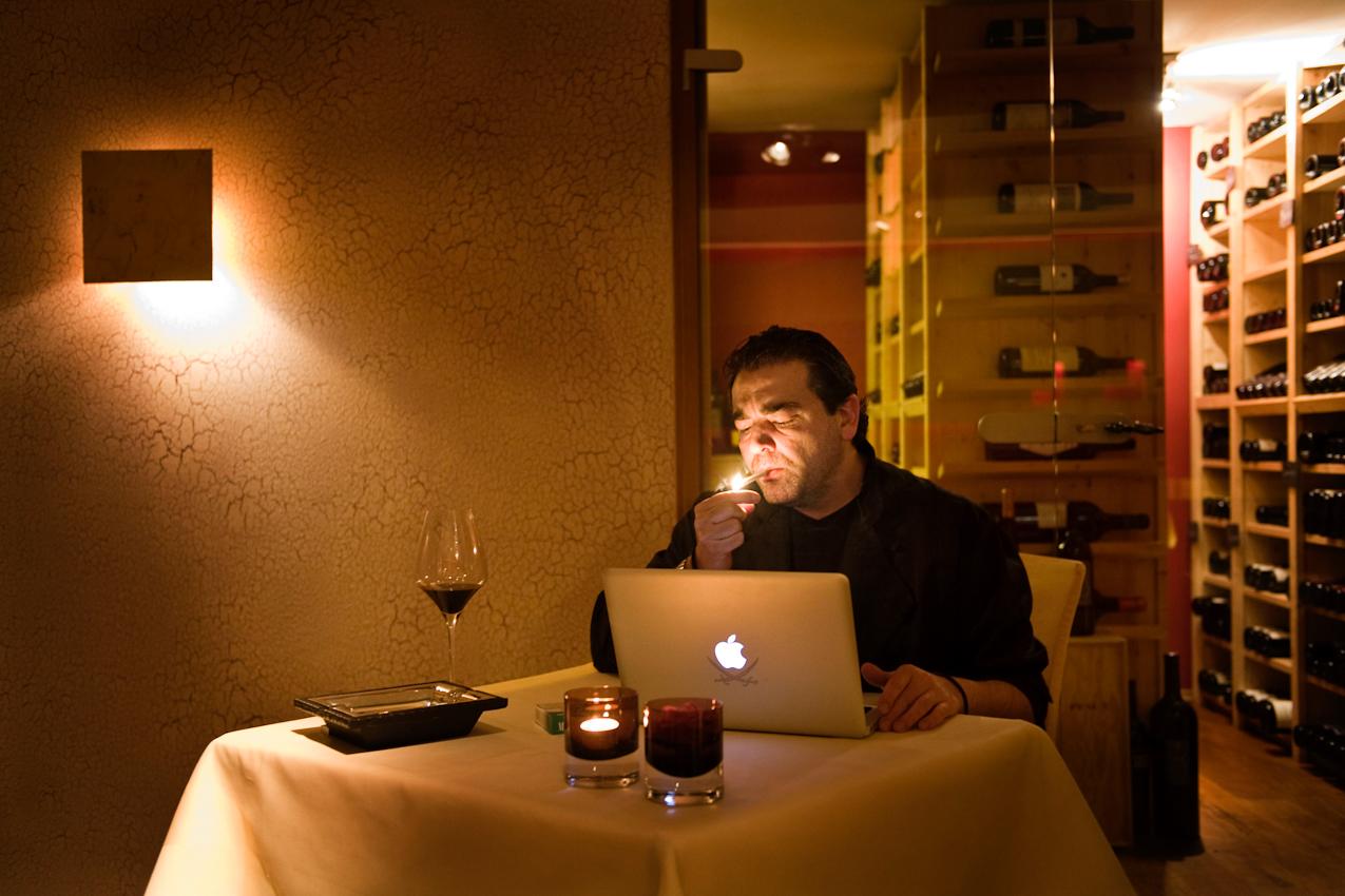 """Der drei Sterne Koch Juan Amador, der in einem Loft im Stadtteil Fechenheim in Frankfurt am Main wohnt, macht am späten Freitag Abend, 07.05.2010 nach einem langen Arbeitstag das erste Mal Pause in seinem Restaurant """" Amador """" in Langen bei Frankfurt. Wie nach jedem Arbeitstag, trinkt er dann ein Glas ausgewählten Rotweins, zündet sich eine Zigarette an und beginnt dann den Email Verkehr des Tages abzuarbeiten. Im Hintergrund sieht man den begehbaren temperierten Weinschrank des Restaurants."""