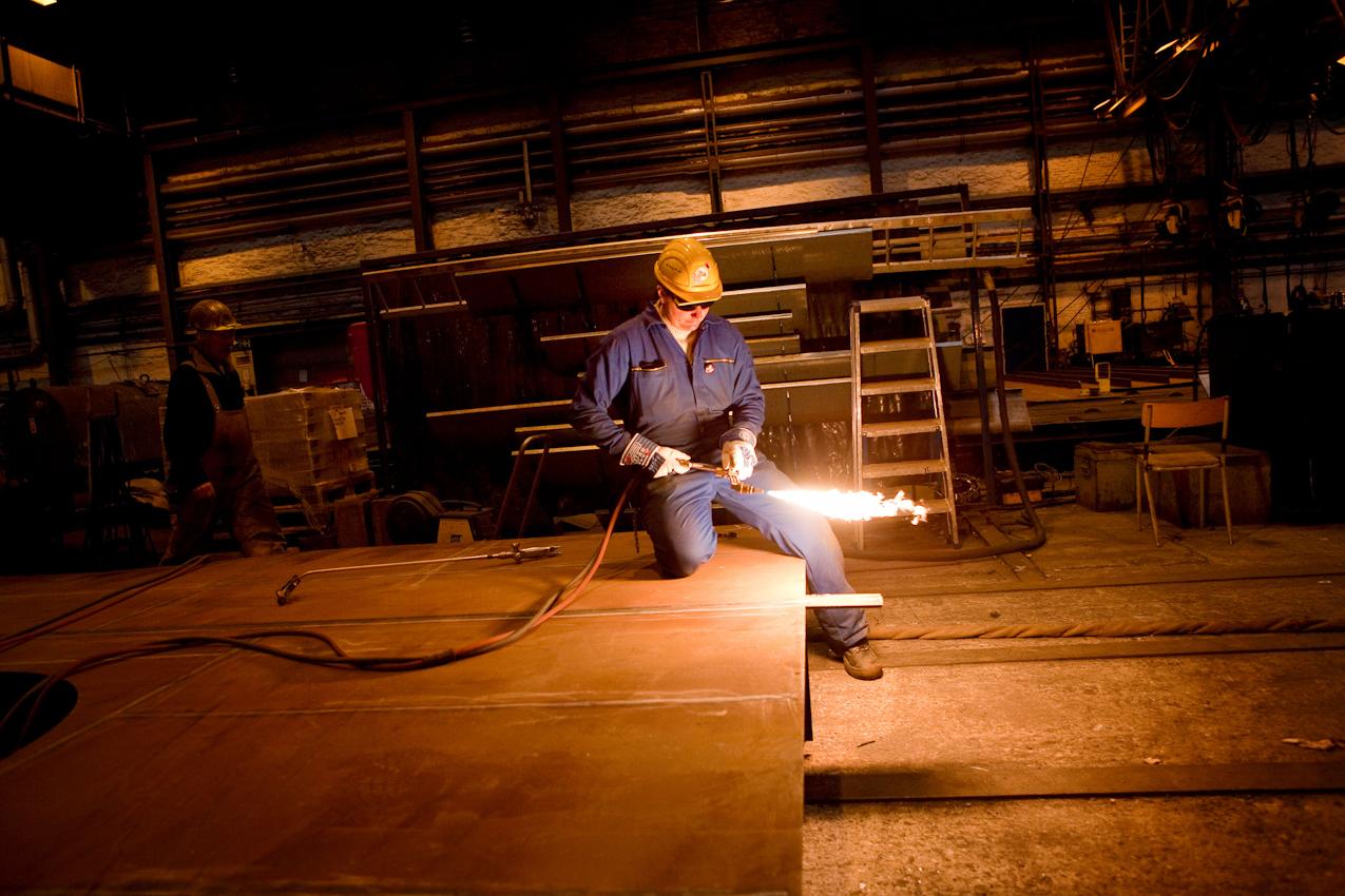 """Auf der Traditionswerft """"Flensburger Schiffbau-Gesellschaft"""" wurden seit 1872 uber 700 Schiffe gebaut. Die Werft ist mittlerweile eine der produktivsten Werften in Deutschland und hat sich auf den Bau von RoRo-Schiffen spezialisiert. Der Werftarbeiter Thorsten Frehse entzündet seinen Gasbrenner um einzelne Metallelemente unter extremer Hitze auszubeulen."""