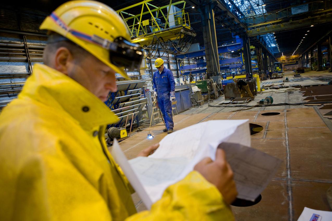 """Auf der Traditionswerft """"Flensburger Schiffbau-Gesellschaft"""" wurden seit 1872 uber 700 Schiffe gebaut. Die Werft ist mittlerweile eine der produktivsten Werften in Deutschland und hat sich auf den Bau von RoRo-Schiffen spezialisiert. In der Vorfertigung werden einzelne Stahlelemente  bearbeitet, bevor sie in der Endmontage zum Schiffsrumpf zusammengesetzt werden."""