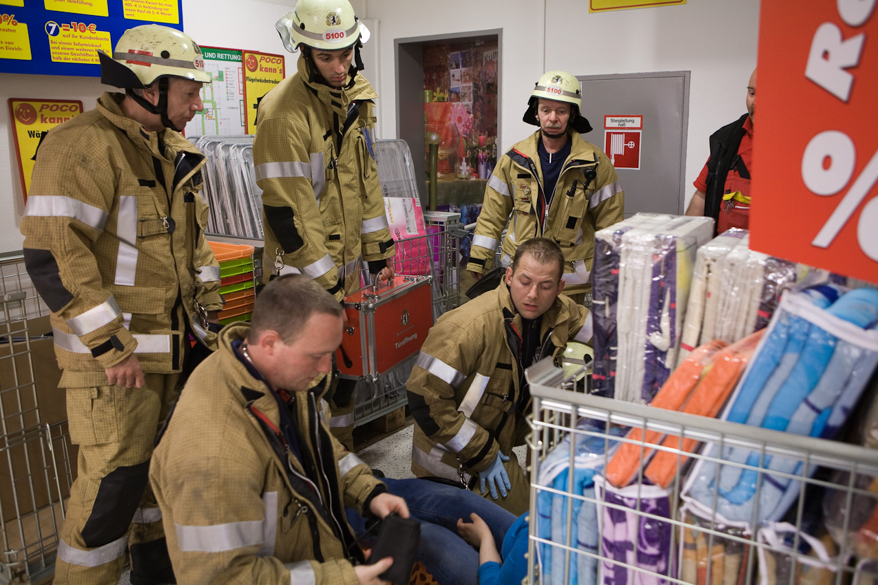 Feuerwehrmanner der Feuerwache Neukölln versorgen eine Person mit Kreislaufproblemen, die längere Zeit in einem Aufzug eingeschlossen war.