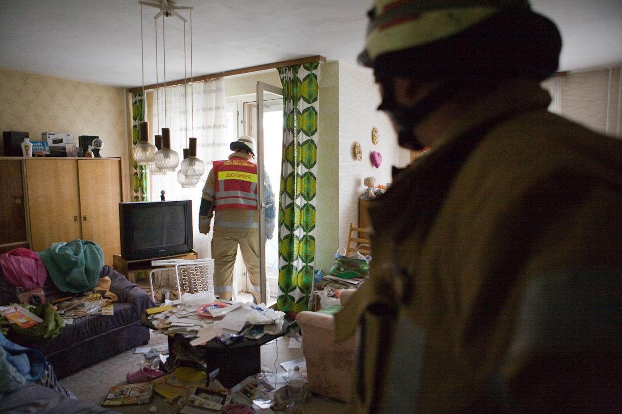 Eine altere Bewohnerin eines Mehrfahmilienhauses in Berlin wurde seit einiger Zeit nicht mehr angetroffen. Daher wurde von den Nachbarn die Feuewehr alarmiert. Nachdem die Feuerwehrleute  die Wohnungstür geöffnet haben, wird die Wohnung nach der vermissten Person abgesucht.