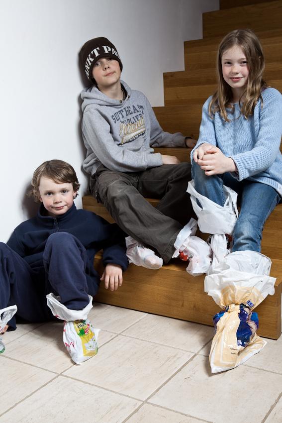 Linus, Moritz und Luca haben sich auf's Trampolinspringen vorbereitet und Plastiktuten an den Füßen befestigt