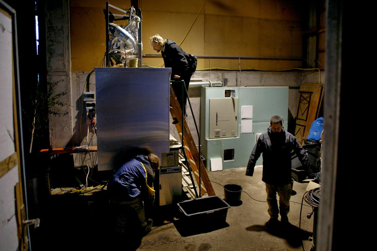 Jettingen, BaWu, Deutschland: Auf dem Bauernhof eines Freundes wurde die Versuchsanlage aufgestellt. Hier verbringen die Wissenschaftler von Addlogic Labs Tage und Nächte um eine Probe nach der anderen zu untersuchen. Technischer Leiter Ulrich Hafen (links) holt die Kohle aus dem Reaktor, warend Physiker Dr. Burkhard von Stackelberg (mitte) uber eine Offnung im Reaktor die Arbeiten überwacht. Wärmeingenieur Michael Klotsche (rechts) wartet auf seinen Einsatz.