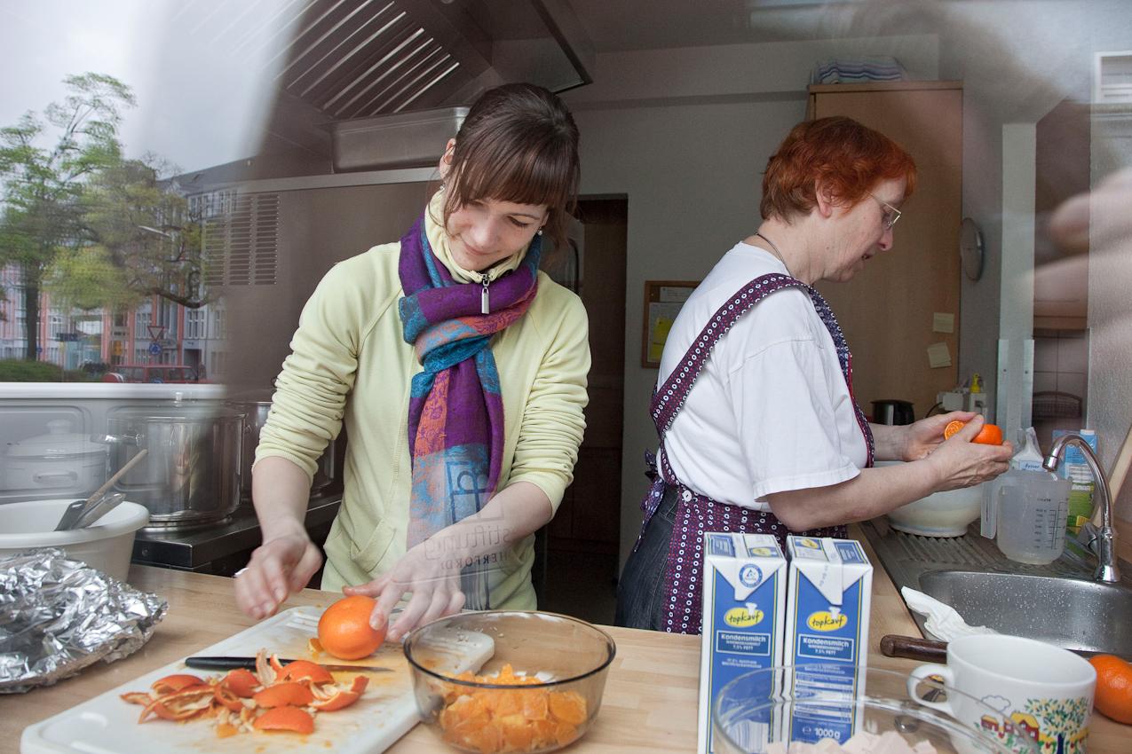 """Schwester Ingrid ist eine Sarepta Schwester und leitet seit 2004 den """"Herforder Mittagstisch e.V."""".  Anika ist Gast beim Mittagstisch und hilft oft gerne in der Küche mit. Projekt A: Herforder Mittagstisch e.V., Medizinische Hilfe für Bedürftige e.V., Sozialberatungsdienst. Ehrenamtliche Helfer der Herforder Petri-Gemeinde bewirten seit über 10 Jahren bedürftige Menschen jeden Tag an einem gedeckten Tisch. Im gleichen Haus sitzen auch die Profis des Sozialberatungsdienstes. Einmal die Woche bieten ehrenamtlich arbeitende  Ärztinnen Sprechstunden an."""