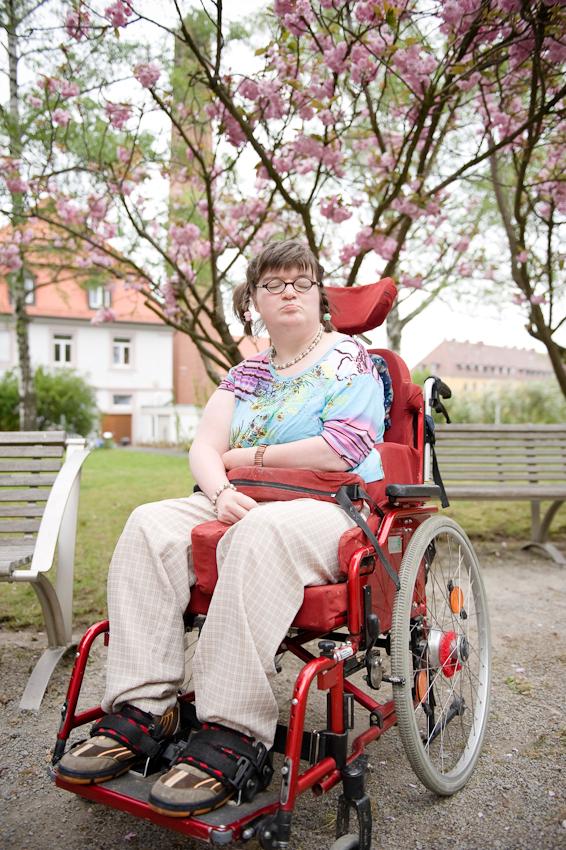 Nicole Spiegel ist eine Bewohnerin des Jakob-Riedinger-Hauses in Würzburg, einem Wohn- und Wohnpflegeheim für Menschen mit Behinderung. Der Bezirk Unterfranken hat sich die psychiatrische und neurologische Versorgung der unterfränkischen Bevölkerung zur wichtigsten gesundheitspolitischen Aufgabe gemacht. Nicole zeigt, wie sie wohnt und lebt. Sie sitzt gerne im Garten des Heims unter den Bäumen.