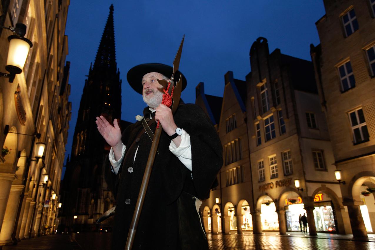Der Münsteraner Nachtwächter fuhrt Touristengruppen durch die abendliche Innenstadt. Hier erzählt er historische Begebenheiten zwischen den Giebelhäusern am Prinzipalmarkt.
