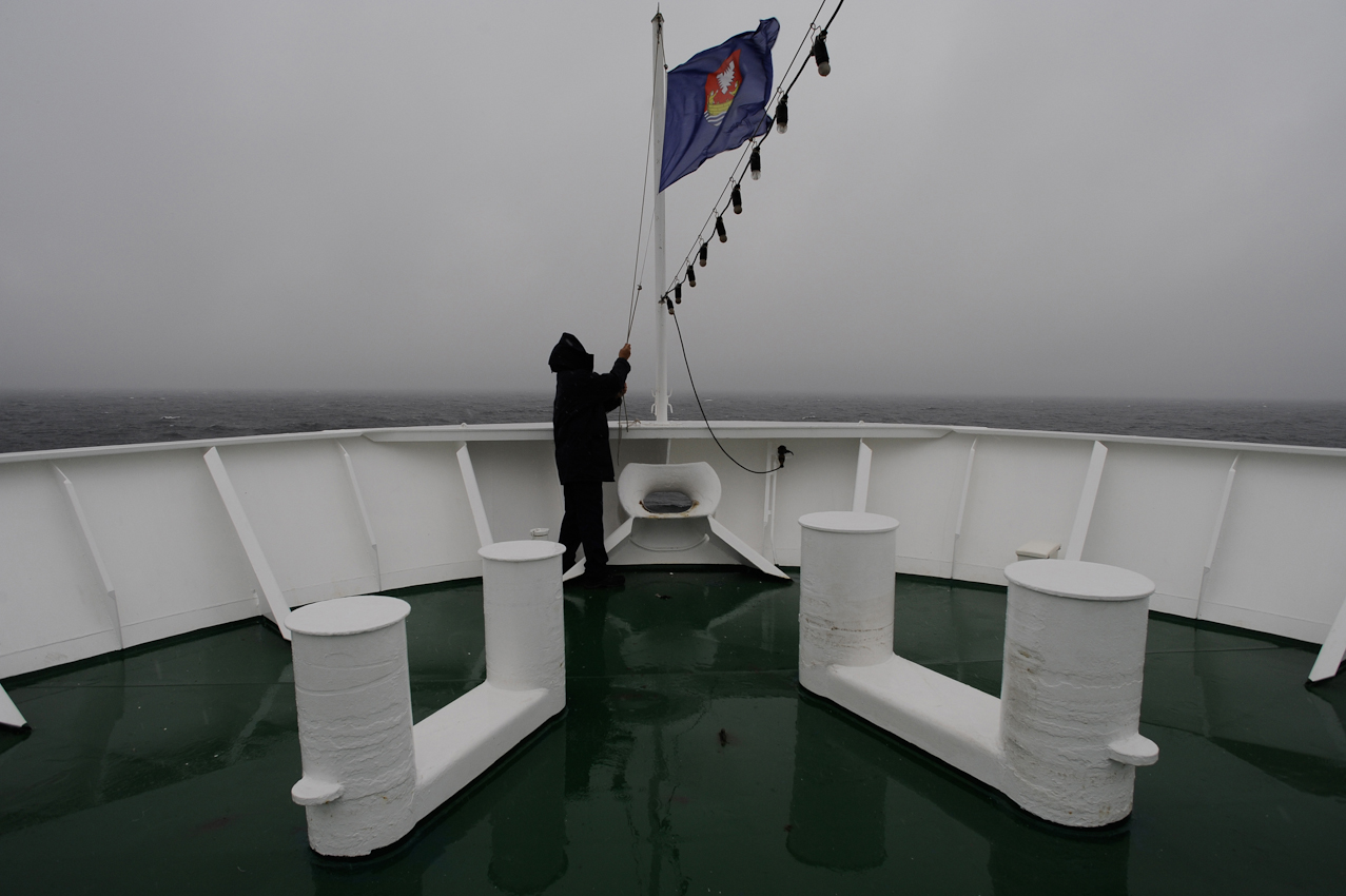 Das Kreuzfahrtschiff MS Deutschland in der rauhen Ostsee ( Windstärke 8 ) auf dem Weg nach Gdynia, Polen. Besatzungmitglied holt die Flagge des Heimathafens Neustadt in Holstein ein.