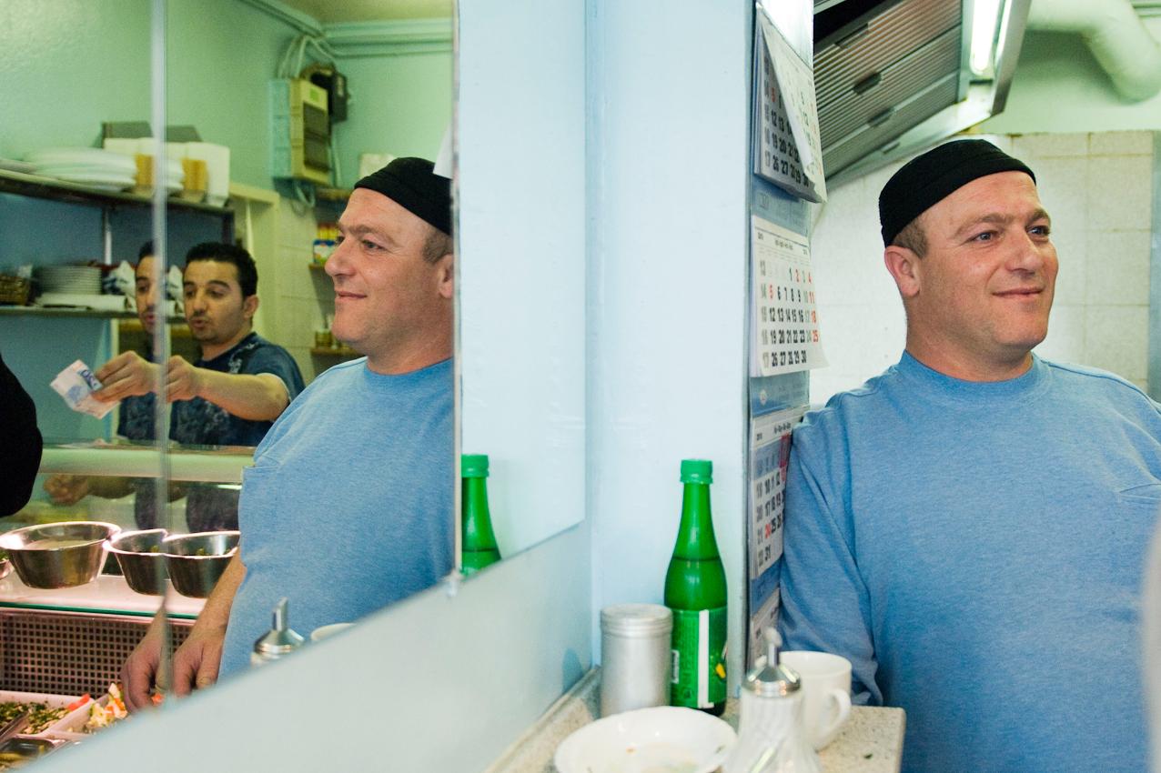 Der Fisch und Fleisch Imbiss JASMINA liegt im Herzen der Gewerbemeile am Hammer Deich im Stadtteil Hamm-Sued. Der palaestinensische Inhaber macht gerade eine kleine Pause. Sein Mitarbeiter kassiert waehrenddessen. Falafel, Pizza, Spie?e und Salate stehen auf der Speisekarte. Zur Mittagszeit kommen die Haendler aus den umliegenden Lagerhallen, Gewerbeplaetzen und Geschaeften zum Essen. Sie fuehlen sich hier zu Hause.