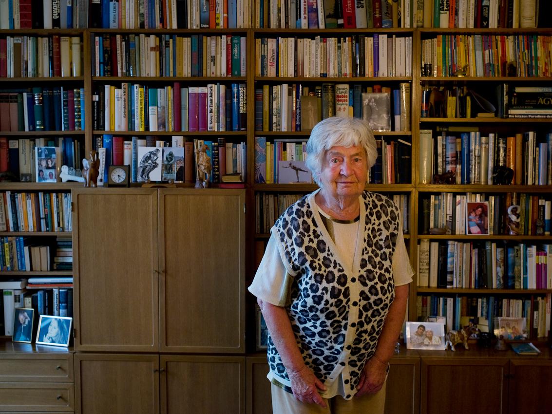 """Ali hat ihr ganzes Leben Bücher geliebt. Seit einigen Jahren musste sie ihr leidenschaftliches Reisen in Europa und der Welt aufhören und liest ihre Bucher erneut. """"Um mein Gedächtnis lebendig zu halten lese ich viel englische Bücher und gute Reiseliteratur. Du weißt ja, ich habe nach dem Krieg beim Engländer und danach bei PanAm gearbeitet"""", sagt Ali zu mir. Sie wollte unbedingt vor ihrem Bücherregal fotografiert werden. Annelise Moldenhauer, 95, in ihrem Wohnzimmer in 25899 Klixbüll, Nordfriesland am Freitag, den 7. Mai 2010."""