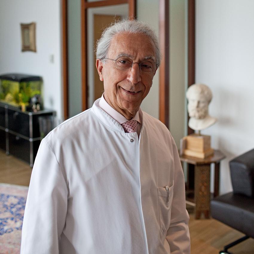 Neuchirurgischer Eingriff am offenen Gehirn, Prof. Samii vom INI Hannover. Beginn eines Arbeitstages. Prof. Samii schon im weißen Kittel in seinem Büro im INI. Für meine Reportage begleite ich für ein paar Stunden den heute 72-jährigen Neuchirurgen Prof. Dr. Madjid Samii. Der gebürtige Iraner ist seit über 45 Jahren auf dem Gebiet der Neurochirurgie tätig und einer der führenden Neurochirurgen. Das von ihm gegründete International Neuroscience Institute (INI) in Hannover ist eine der modernsten Neurokliniken der Welt.  In seiner ersten Operation am Vormittag des 7. Mai entfernte Prof. Samii und ein 8-köpfiges Team einer Frau einen Tumor aus dem Gehirn. Um den Tumor möglichst radikal aber schonend entfernen zu können, wurde das Gehirn der Patientin zuvor in einem Kernspintomographen vermessen. Die so mit modernster Neuronavigation durchgeführte Operation verlangte über Stunden absolute Konzentration und Präzision. Die freistehende Arbeit erfordert nicht nur geistige sondern auch absolute körperliche Fitness.