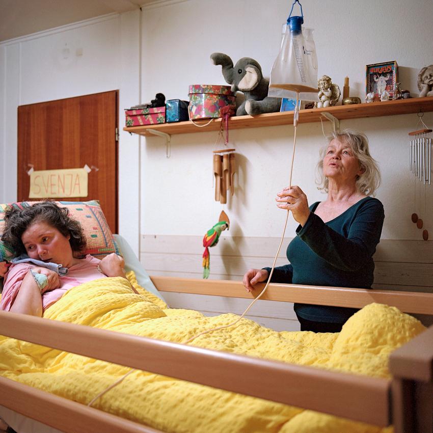 """""""Frühstück, Schnecke!"""". Die seit 18 Jahren im Wachkoma lebende Svenja wird am 07.05.2010 von ihrer Mutter, Helga, zum Frhstück im Bett über eine Ernahrungssonde versorgt. Svenja lebt bei ihrer Mutter in Hannover. Die 66-jährige kümmert sich rund um die Uhr um ihre Tochter. Komapatienten sind auf intensive Hilfe und Zuwendung von Seiten ihrer Angehörigen angewiesen. Häufig sind sie diejenigen, die mit viel Zuneigung und Geduld einen kleinen Zugang zum Bewusstsein des Betroffenen finden. Svenja fiel 1992 in Mexiko nach einem Reitunfall ins Wachkoma."""