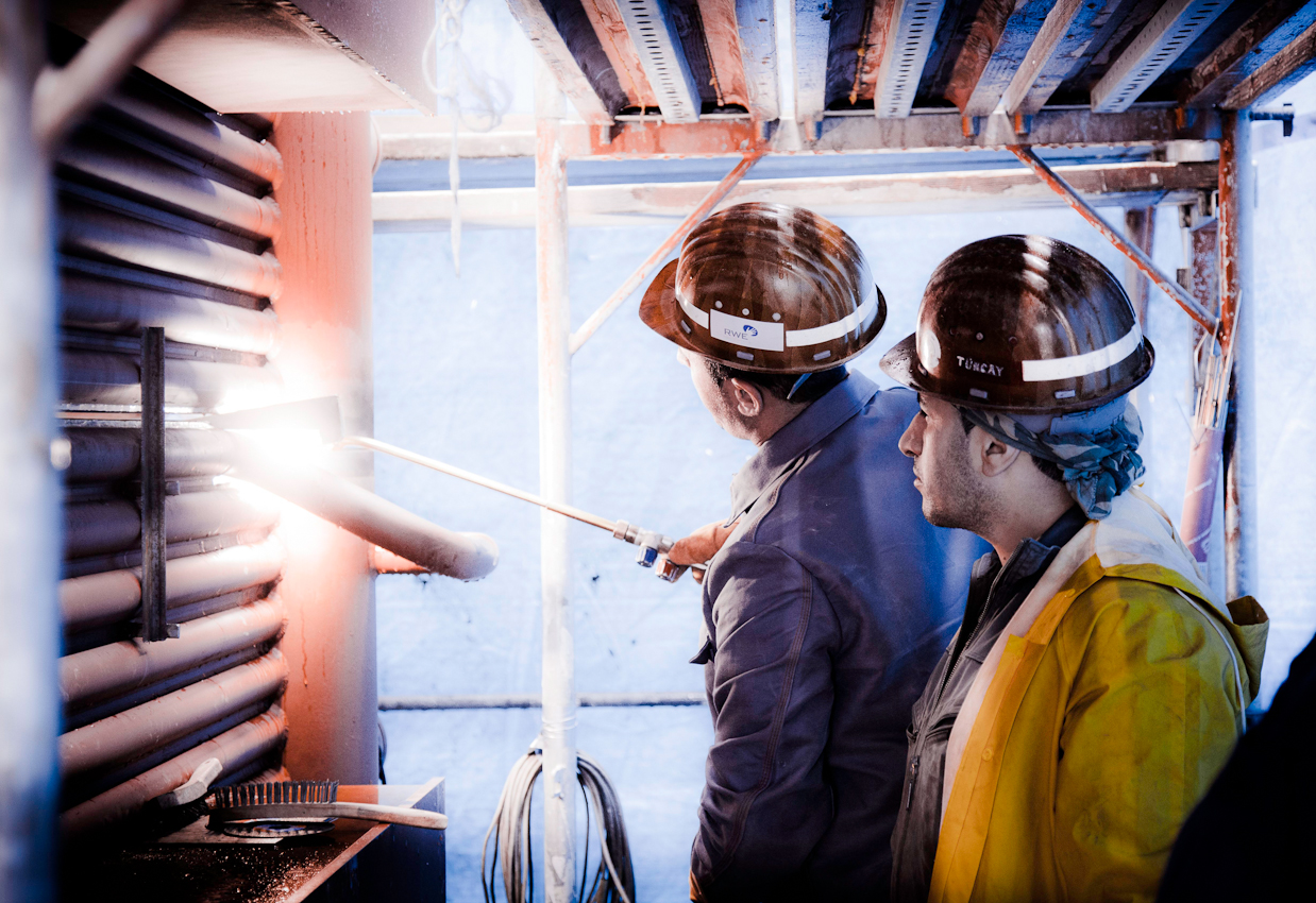 Zwei Arbeiter bereiten eine Schweissnaht vor. Im Bonner Heizkraftwerk werden Vorbereitungen für den Einbau des neuen Heizkessels getroffen.