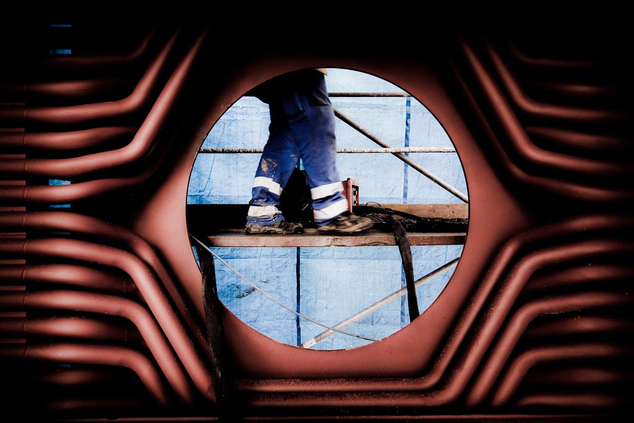Ein Arbeiter steht auf einem Gerüst hinter einer der Brenneröffnungen, vor dem neuen Heizkessel. Im Bonner Heizkraftwerk werden Vorbereitungen für den Einbau des neuen Heizkessels getroffen.