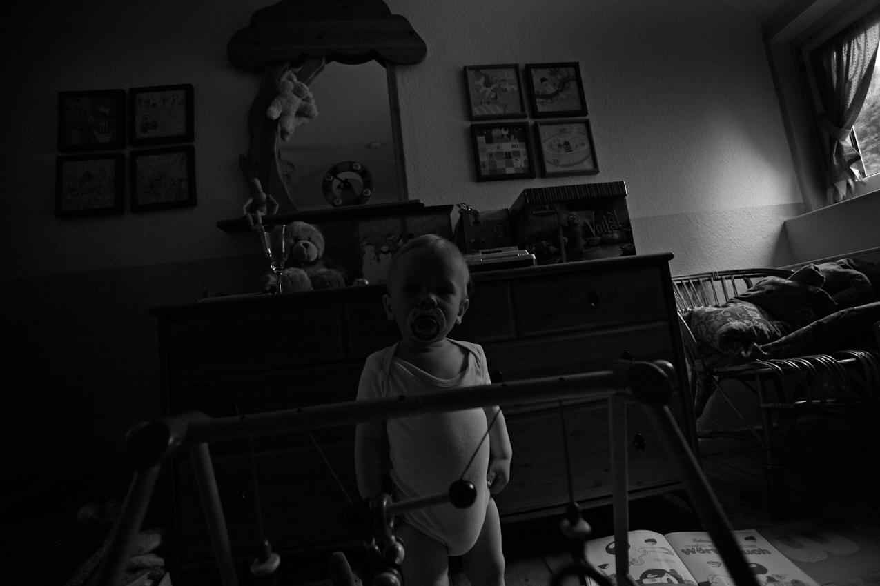 Elias steht in seinem Spielzimmer und blickt in die Kamera. ----- Titel:  Ganz bei sich -- Ein Tag im Leben von Elias Valentin Morascher; Sohn des Fotografen Arnold Morascher. Mein Hauptinteresse bestand darin, das Kind nicht in Interaktion mit anderen sondern in Konzentration auf sich selbst zu fotografieren. Die Serie zeigt die Eigenständigkeit des 18 Monate alten Kindes (geboren 14.11.2008),  die konzentrierten Momente. Lernen, Erfahren, Bewegung, selbständiges Spielen; auch die Frustration des Kindes, als es z.B. nicht in der Lage ist, alleine auf das Bett der Eltern zu klettern. Die Serie entstand in etwa vier Stunden zwischen 13:00 und 17:00 Uhr am 07.05.2010 und zeigt ein Stück Leben eines Kleinkindes in Deutschland /22175 Hamburg/Bramfeld.