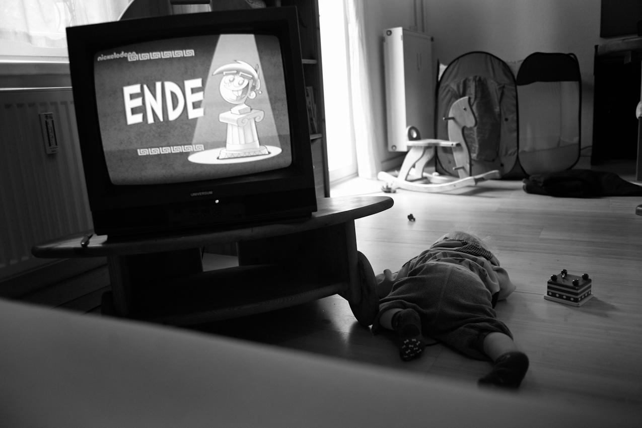 Elias ruht sich neben dem Fernseher aus. ----- Titel:  Ganz bei sich -- Ein Tag im Leben von Elias Valentin Morascher; Sohn des Fotografen Arnold Morascher. Mein Hauptinteresse bestand darin, das Kind nicht in Interaktion mit anderen sondern in Konzentration auf sich selbst zu fotografieren. Die Serie zeigt die Eigenständigkeit des 18 Monate alten Kindes (geboren 14.11.2008),  die konzentrierten Momente. Lernen, Erfahren, Bewegung, selbständiges Spielen; auch die Frustration des Kindes, als es z.B. nicht in der Lage ist, alleine auf das Bett der Eltern zu klettern. Die Serie entstand in etwa vier Stunden zwischen 13:00 und 17:00 Uhr am 07.05.2010 und zeigt ein Stück Leben eines Kleinkindes in Deutschland /22175 Hamburg/Bramfeld.