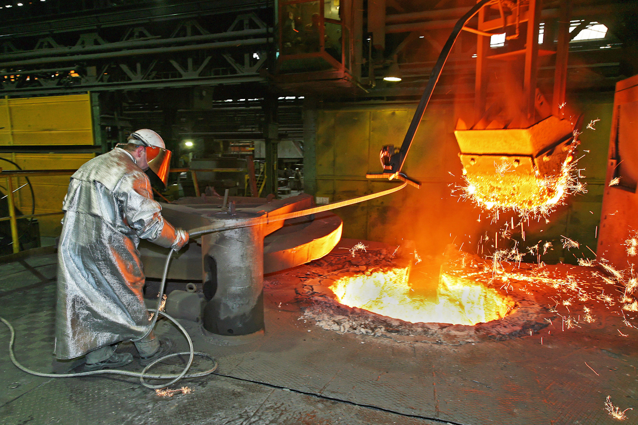 Der Giessereimeister befuellt den Heizofen zur Herstellung von Roheisen mit weiterem Eisenschrott zur Schmelze. Fuer diesen Vorgang muss er den feuerfesten Mantel, Helm mit Blendschutz, Handschuhe, Gamaschen und Schuhe tragen. Das Verfahren in dieser Eisengiesserei wird seit ca. 160 Jahren fast unveraendert fortgefuehrt. Noch heute ist diese Eisengiesserei ein Unternehmen mit kontinuierlichem Absatz. Die Eisengussprodukte dienen meist als Gehaeuse fuer grosse Turbinenanlagen, Kokillen oder Gehaeuse von Schiffsmotoren. Eisenguss in der Eisengiesserei der Friedrich - Wilhelms- Huette in Muelheim / Ruhr