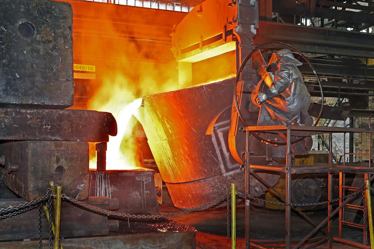 Der Giessereimeister fuellt nun langsam das bis zur Weissglut und 1370 Grad heisse Eisen in die eigentliche Form des Pumpengehaeuses. Mit Hilfe des grossen Drehrades kann der die Fliessgeschwindigkeit und Menge des fluessigen Roheisens steuern. Auf der zu giessenden Form lagern Tonnenschwere Eisenbloecke und den Druck des Gases und des Eisens Stand zu halten. Andernfalls wuerde die Eisenform nach oben weggedrueckt. Danach ist der Giessvorgang beendet und das Gussteil muss bis zu 5 Wochen erkalten.  Das Verfahren in dieser Eisengiesserei wird seit ca. 160 Jahren fast unveraendert fortgefuehrt. Noch heute ist diese Eisengiesserei ein Unternehmen mit kontinuierlichem Absatz. Die Eisengussprodukte dienen meist als Gehaeuse fuer grosse Turbinenanlagen, Kokillen oder Gehaeuse von Schiffsmotoren. Eisenguss in der Eisengiesserei der Friedrich - Wilhelms- Huette in Muelheim / Ruhr
