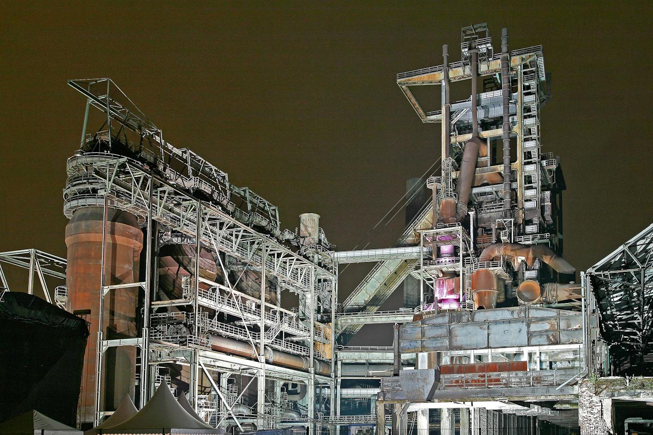 Dortmund - Horde. Hochofenstrasse  --- Der 1998 stillgelegte Hochofen in Dortmund Horde mit dem Namen Phoenix - West ist im Rahmen des Strukturwandels zum Denkmal und Landmarke umfunktioniert. Gelegentlich werden innerhalb des alten Hochofengeländes Events veranstaltet. Etwa open Air Kinoveranstaltungen oder Lichtkunst - Darstellungen. Fur den Besucher ist es ein wichtiger Beststandteil zur alten Industriekultur und deshalb als Denkmal oder Museum unbedingt erhaltenswert. Auch nach den 12 Jahren der Stilllegung werden immer noch weitere Konservierungsarbeiten durchgeführt.