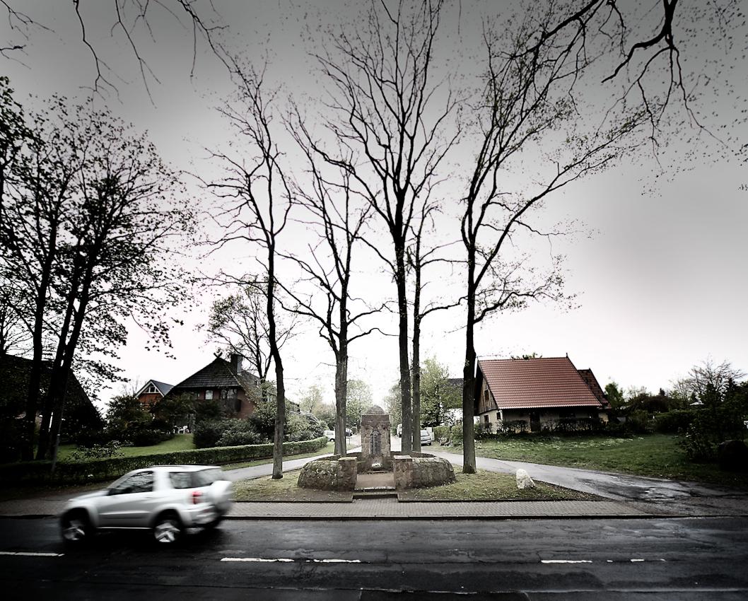 """Kriegerdenkmal in Schierhorn/Hanstedt in der Nordheide am 07. Mai 2010, dem Vortag des Jahrestages der endgültigen Kapitulation des Naziregimes und des Endes des Zweiten Weltkrieges vor 65 Jahren. Am 6. Mai 1945 besetzten britische Truppen erstmals das Heidedorf Schierhorn und blieben laut Ortschronik auch am 07.05.1945 hier in der Orstmitte  anwesend. Gegenwärtig erinnert ein zwischen Eigenheimen, Baulücke und löchriger Durchgangsstraße befindliches kleines Denkmal mit der Aufschrift """"Den treuen in den beiden Weltkriegen gefallenen Söhnen der Gemeinde Schierhorn"""" an die Vergangenheit. Weiteres """"Dorfleben"""" ist an dieser Stelle ausgestorben."""