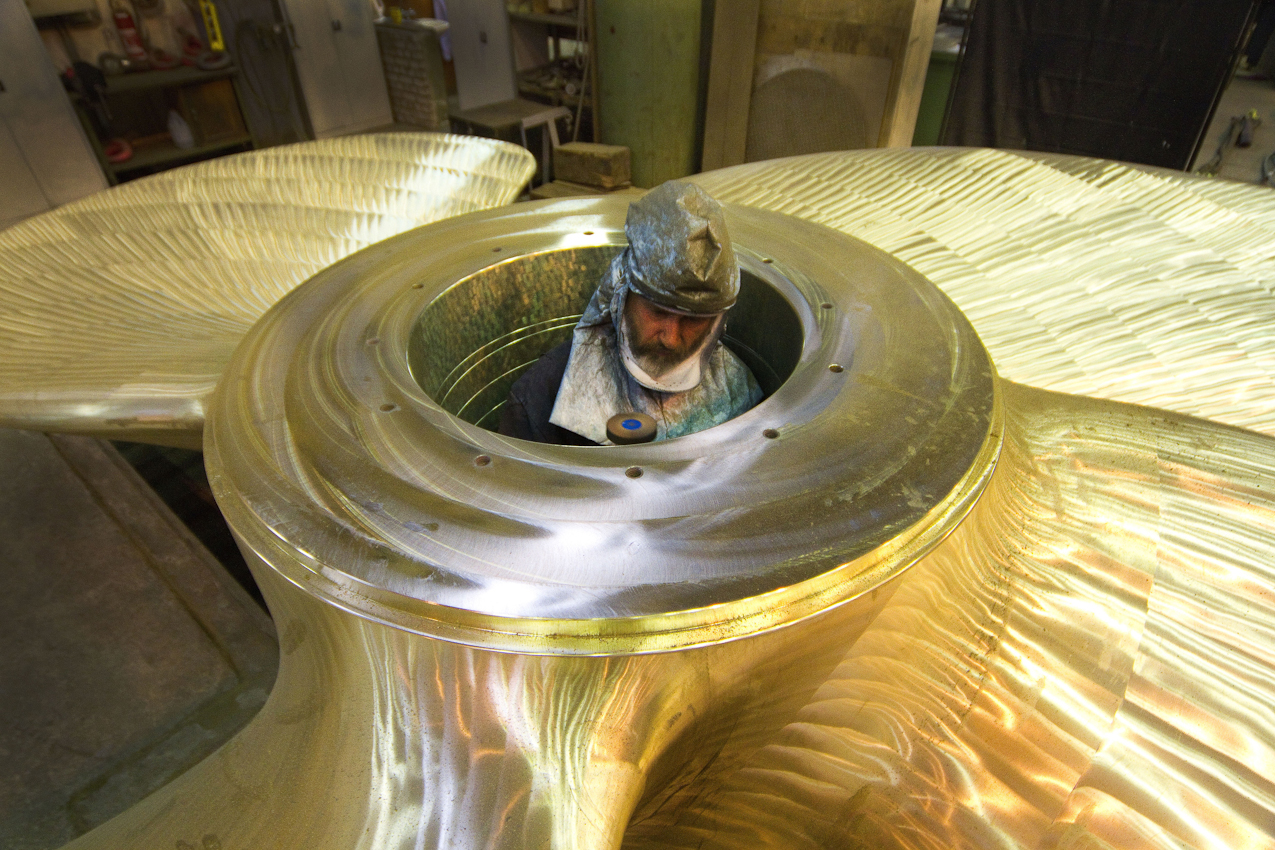 Ein Arbeiter bearbeitet mit der Schleifmaschine die Buchse, in die später die Welle hinein ragt.
