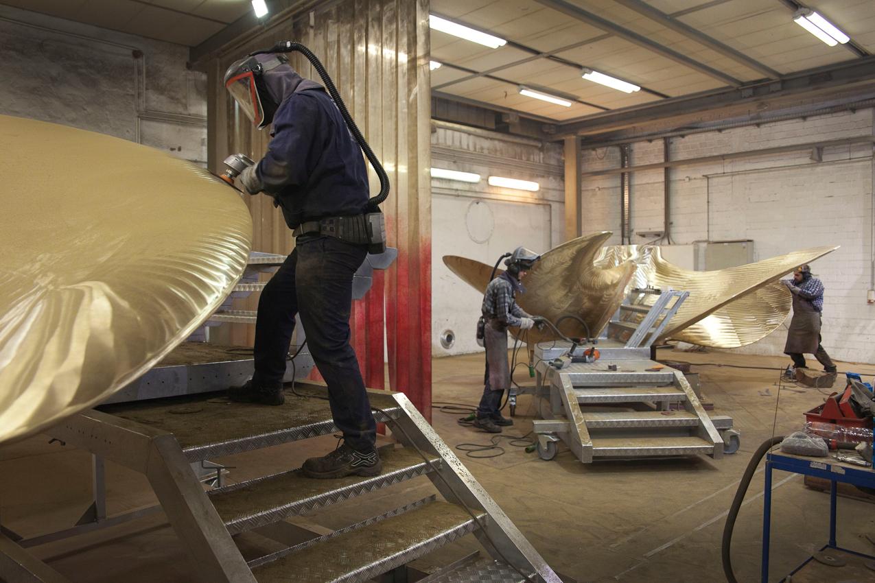 Arbeiter bei Schleifarbeiten an zwei Propellern. Wegen der hohen Entwiclung von Schleifstaub tragen die Arbeiter dabei Schutzmasken.