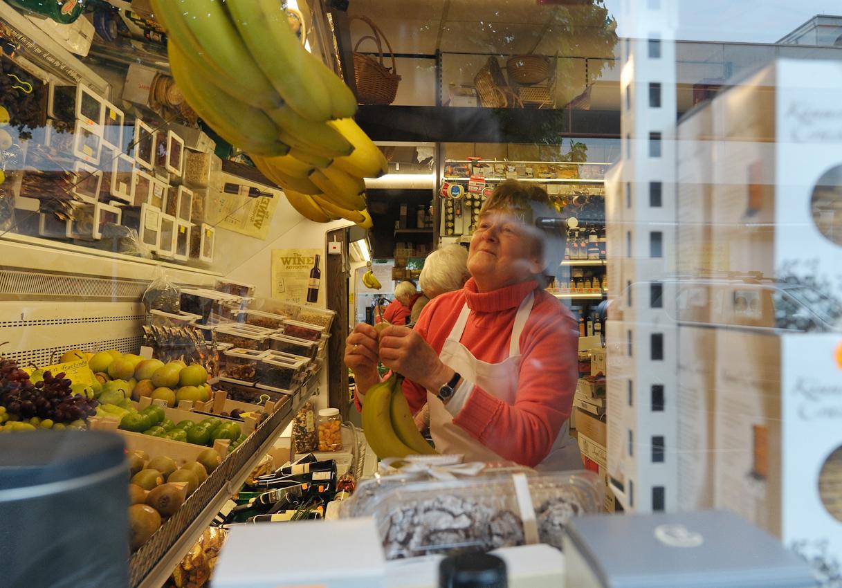 Irmgard Heil, welche gut gelaunt Bananen zum Verkauf an Haken hängt.