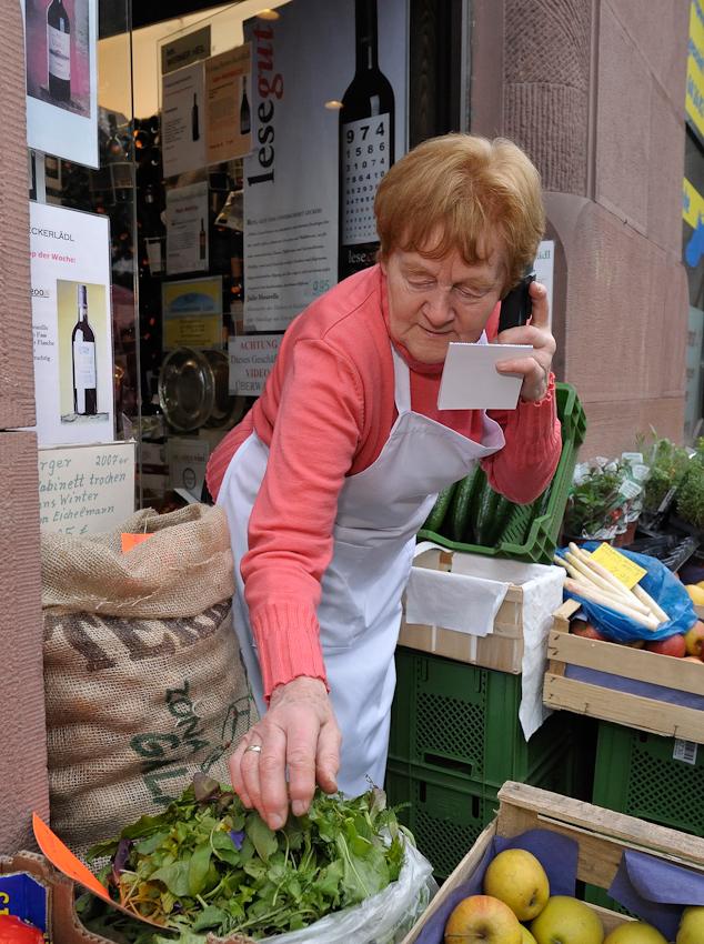 Irmgard Heil telefoniert mit ihrem Großhändler, während sie den Wildblumensalat kontrolliert.