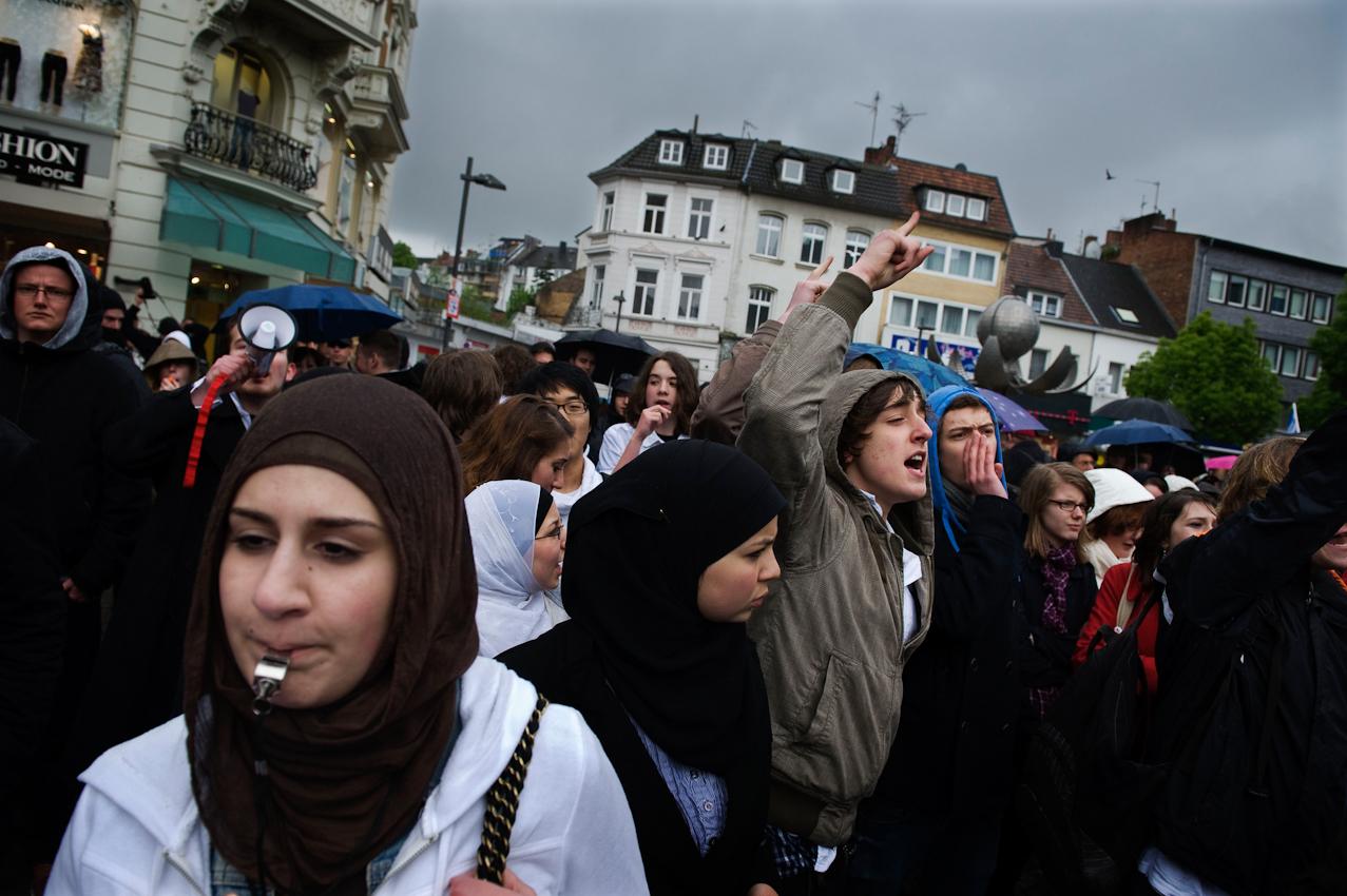 Eine Muslima protestiert mit einer Trillerpfeife und weiteren Demonstranten gegen eine Wahlkampfveranstaltung der Partei pro-NRW im Rahmen der Landtagswahlen in Nordrhein-Westphalen.
