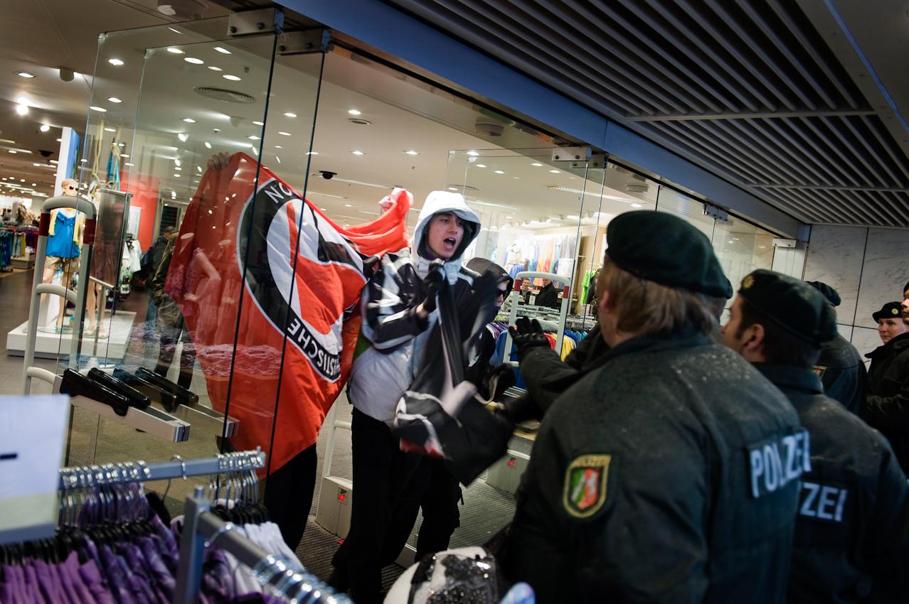 Mitglieder der Antifa Aachen versuchen, aus einem Kaufhaus kommend eine Wahlkampfveranstaltung der Partei pro-NRW zu stören und werden dabei von der Polizei aufgehalten.
