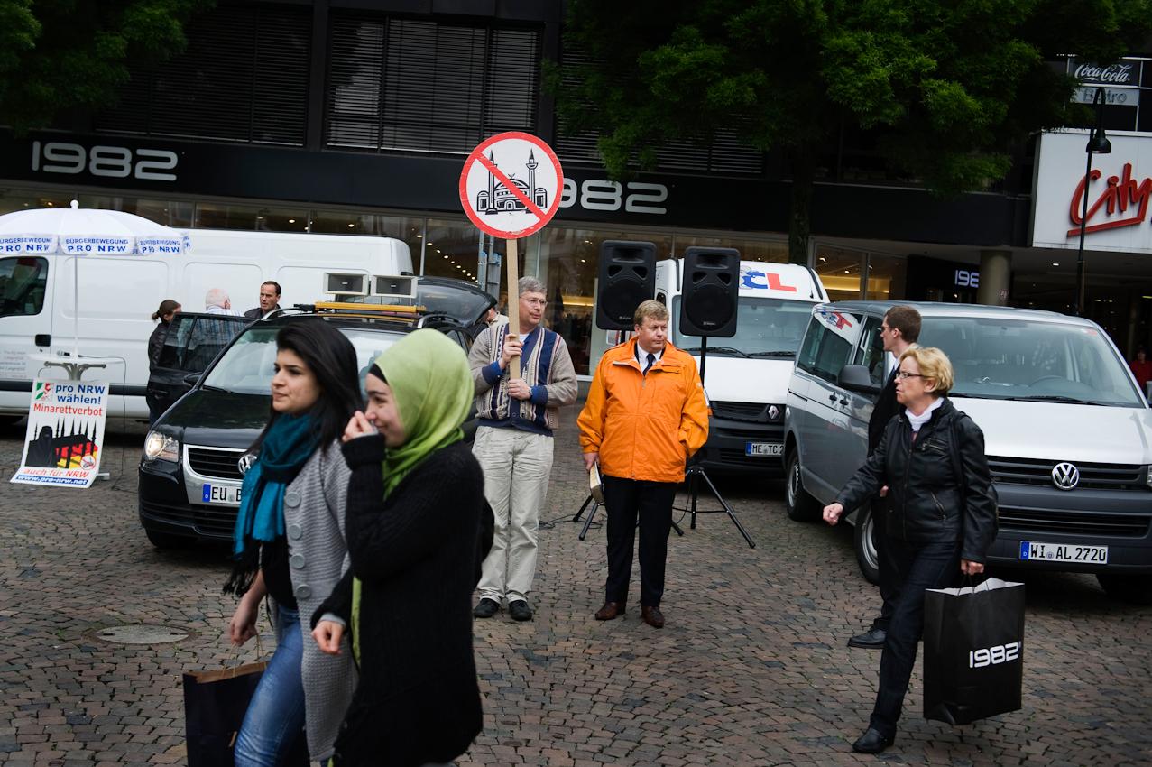 Passanten laufen während einer Wahlkampfveranstaltung auf dem Markt vor dem Rathaus in Aachen an Mitgliedern der Partei pro-NRW mit Schildern einer durchgestrichenen Moschee entlang.