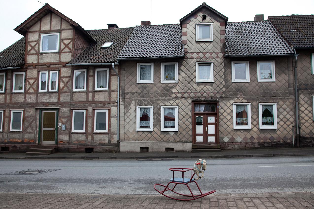 Weserbergland, Stadtoldendorf, Deenser Straße, 12:08 Uhr. Straßenzug mit alten Fachwerkhäusern und Schaukelpferd (vorgefunden).