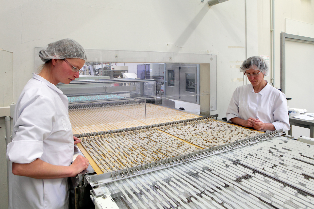 Zwei Bandarbiterinnen beobachten die Produktionsbänder mit Erfrischungsstäbchen.