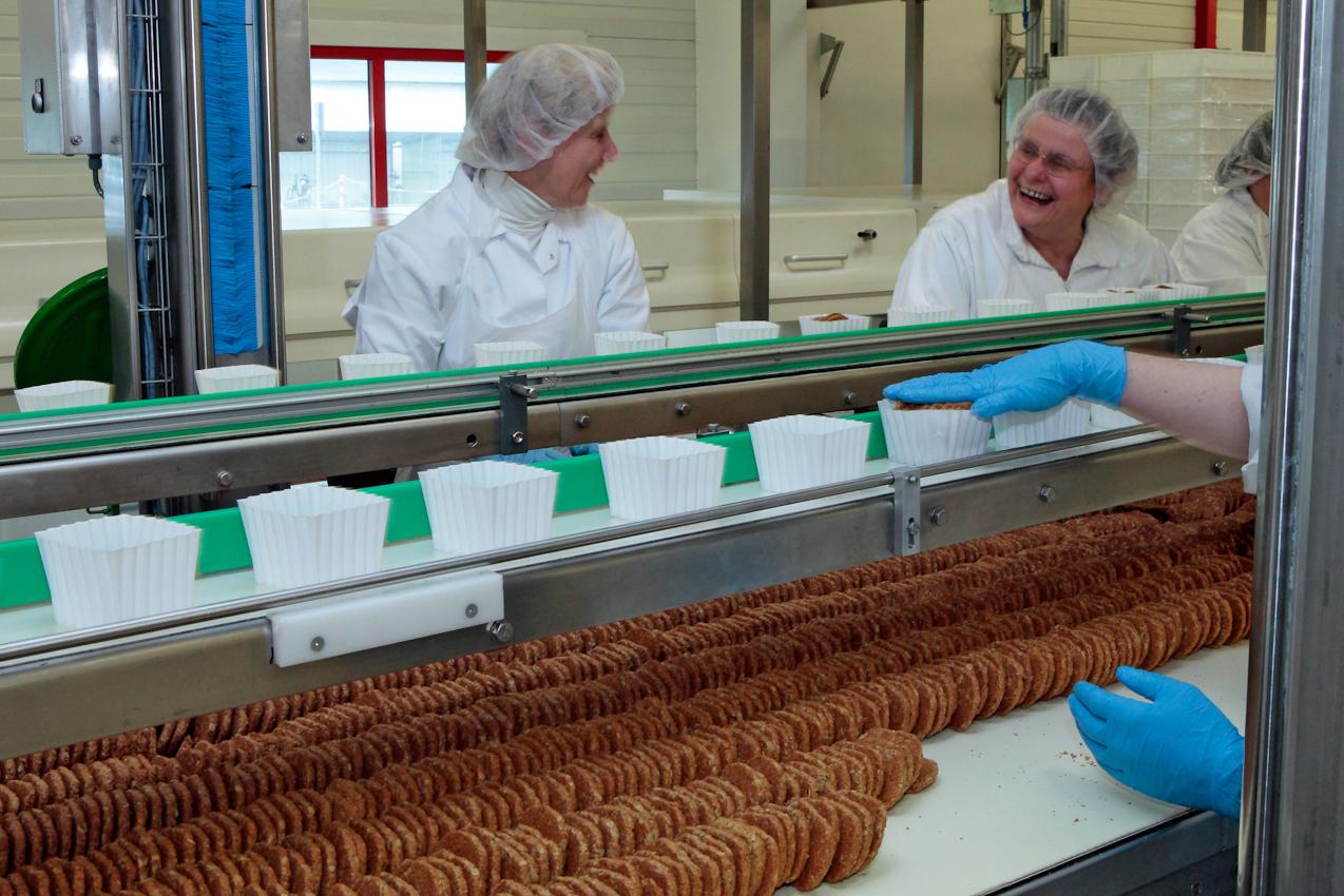 Arbeiterinnen verpacken Haferflockenkekse.