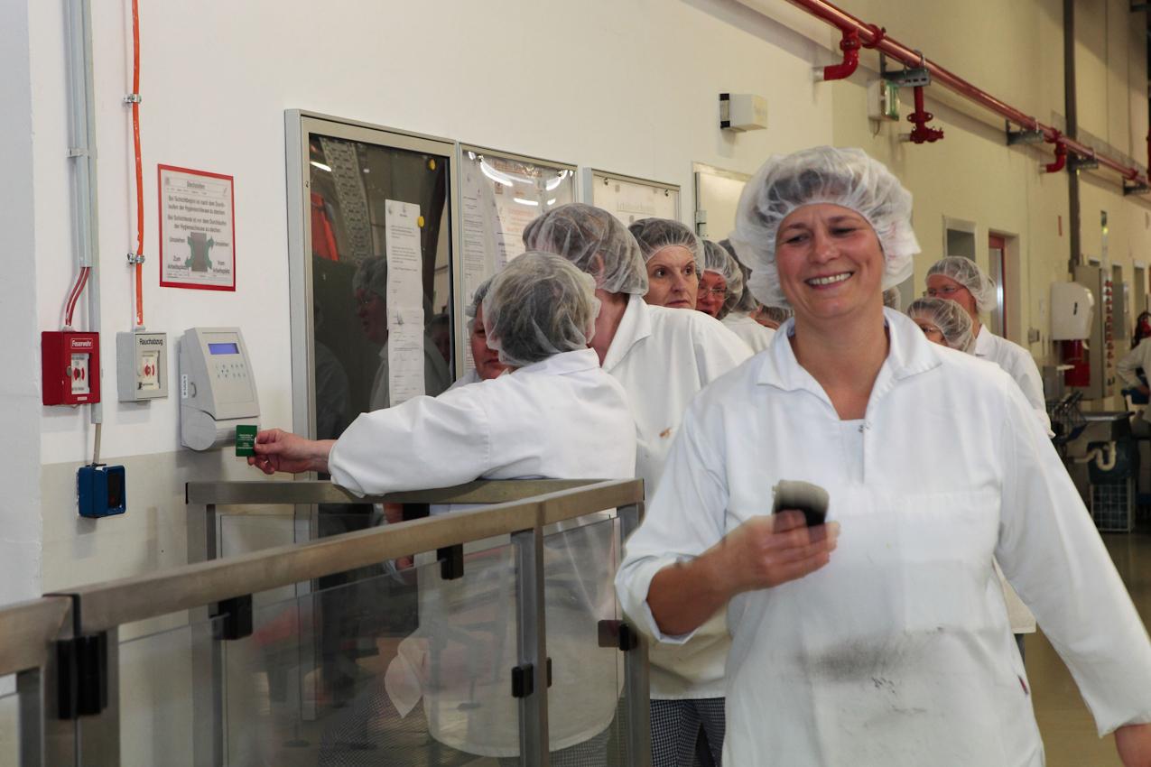 Endlich Feierabend! Arbeiterinnen am Ende ihrer Schicht an der Stechuhr.