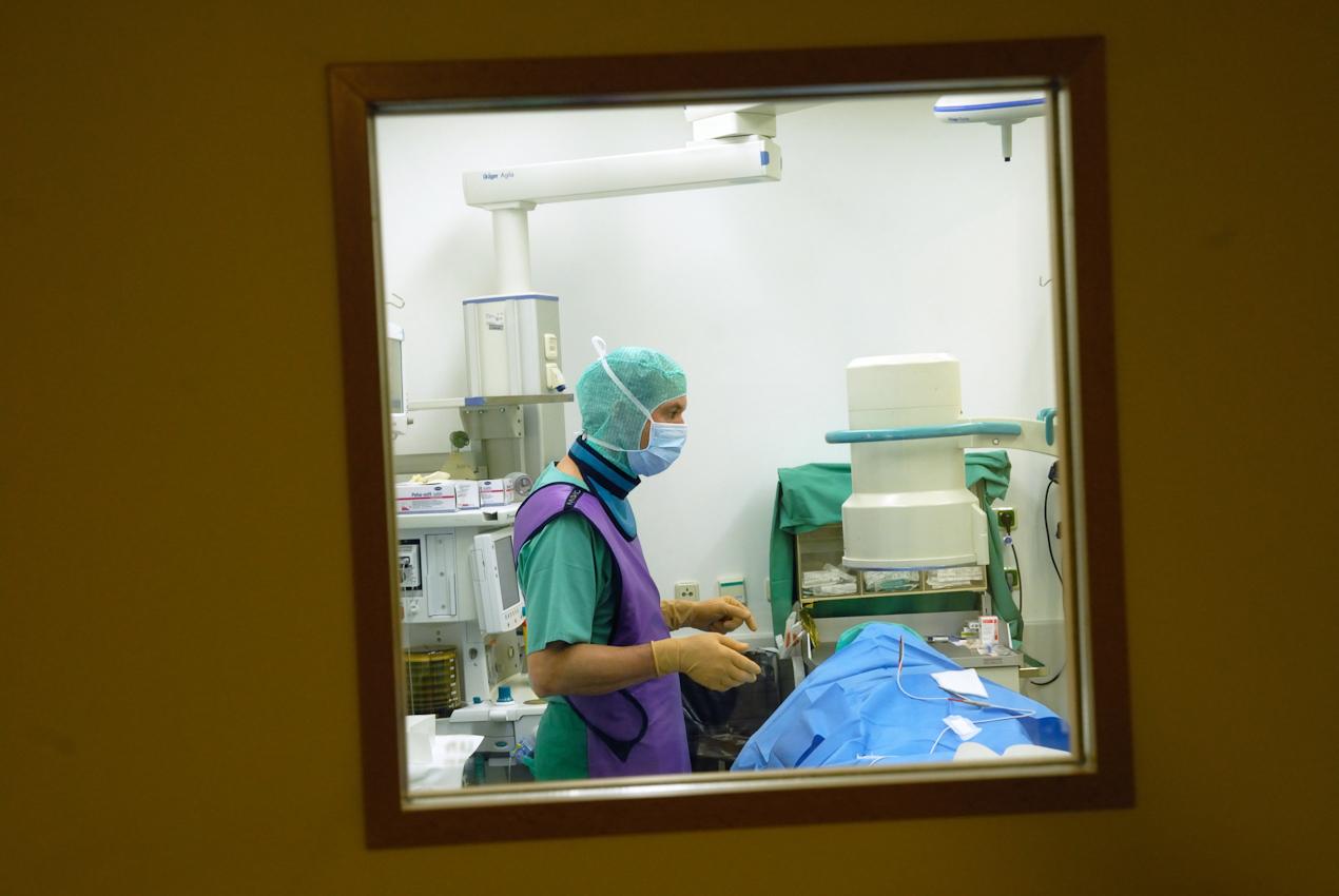 Oberarzt Dr. Ulrich Böhling, Orthopäde und Unfallchirurg mit Bleiweste hinter der Strahlenschutztür des Gipsraumes. Nervenwurzeln werden unter dem Röntgengerät lokalisiert und infiltriert.