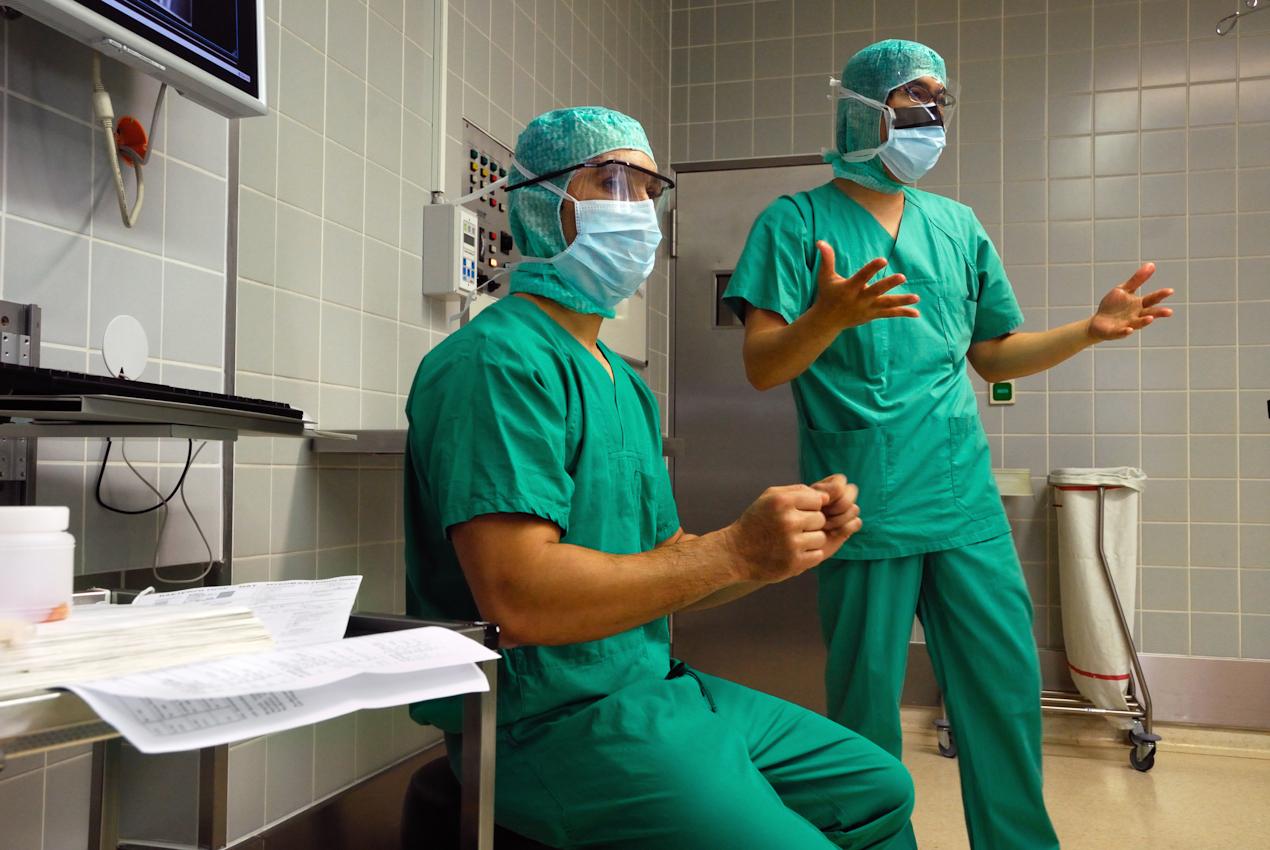 Chirurgen im Operationssaal der Klinik für Orthopädie vor einer Hüftoperation. Ihre Arme wurden desinfiziert und müssen schnell an der Luft trocknen, bevor sterile Handschuhe darüber kommen.