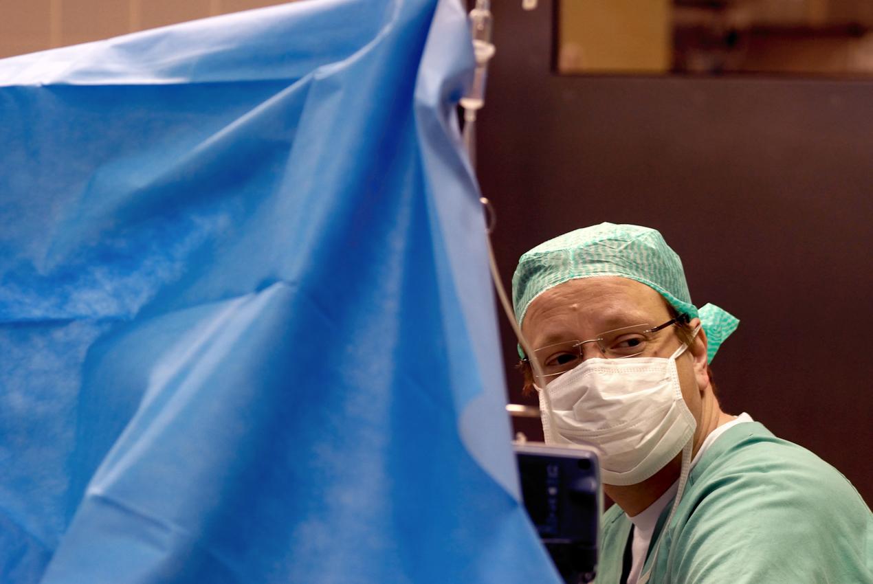 """Der Anästhesist sitzt während einer Hüftoperation hinter der """"Blut-Hirn-Schranke"""". Das blaue Tuch trennt im Operationssaal die Chirurgen von den Anästhesisten."""