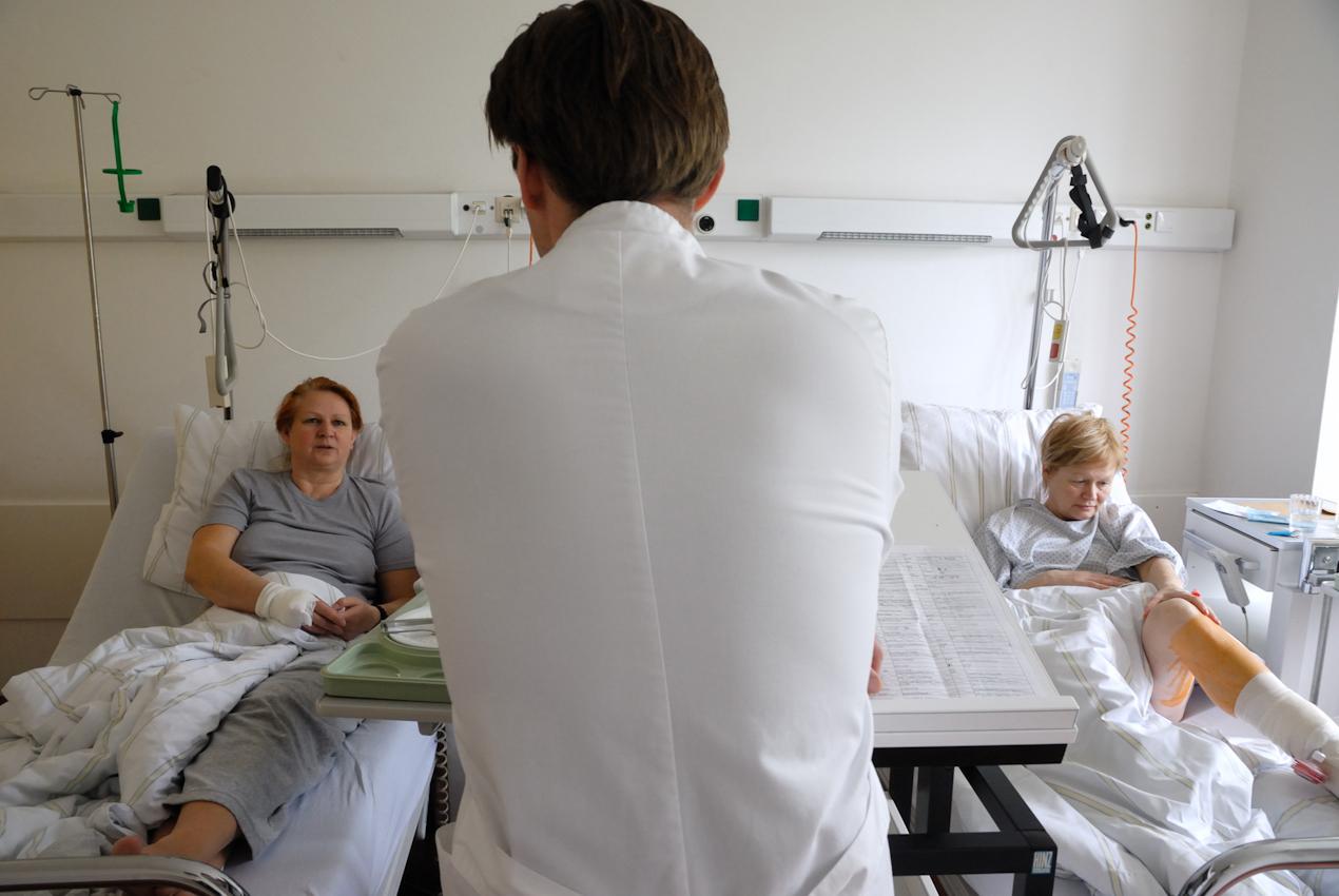 Visite auf der unfallchirurgischen Station. Stationsarzt Dr. Sebastian Canarius hinter Krankenakten, spricht mit seinen Patientinnen nach chirurgischen Eingriffen.