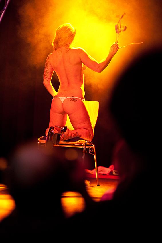 Ein Erotik-Modell stript auf einer der drei Bühnen.