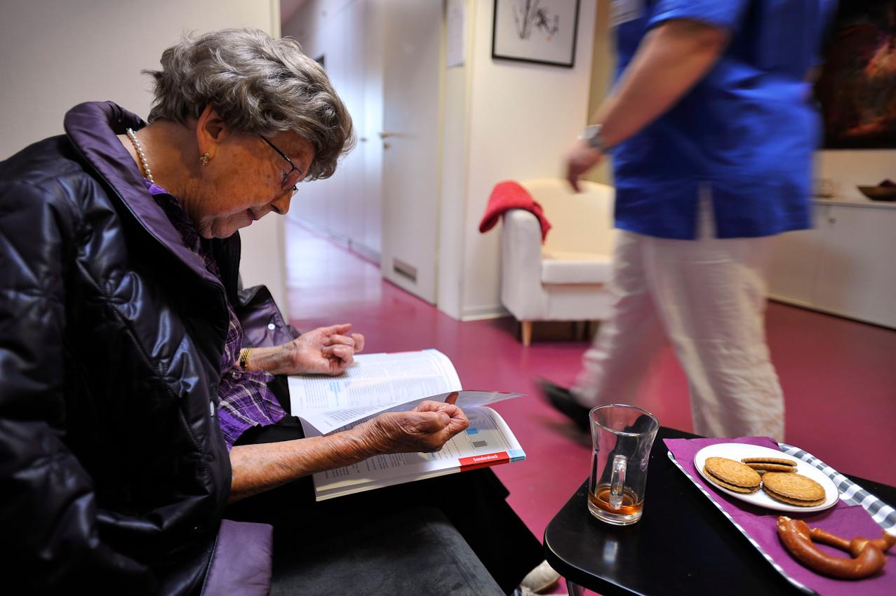 """Für die aktuelle Situation der 91-jährigen Patientin stehen im Vordergrund: Der altersbedingte Muskelabbau / Muskelschwäche mit Sturzgefahr chronische Schmerzen der Wirbelsäule (eigentlich der Muskeln, Sehnen und Bänder um die Wirbelsäule herum), die Osteoporose, die schon mehrfach zu Knochenbrüchen geführt hat. Die Wirbelsäule hat osteoporosebedingte Knochenbrüche an 2 Lendenwirbeln (L1 und 3) erlitten, und hat degenerative Veränderungen (Spondylosios deformans), die zu Schmerzen und Verspannungen führen. Sturz und Osteoporose sind zusammen ein unheiliges Paar, das zu Knochenbrüchen führt, die jedes Mal die Sturzangst, Bewegungsangst verstärkt, die Wirbelsäule deformiert, chronische Schmerzen hervorrufen kann. Auch die Blutgefäße sind nicht mehr jung. Bei einem Bluthochdruck, der schon zu krisenhaften Blutdruckentgleisungen geführt hat, bestehen auch Durchblutungsstörungen der Beine. Es ist erstaunlich, wie jung und fit sie mit ihren 91 Jahren wirkt, trotz der vielen schweren Erkrankungen. Die Depression lasst sie sich nicht anmerken.  Die 91-jährige Patientin im Wartebereich. Sie liest eine Fachzeitschrift!  Im Vordergrund einige Kekse und ,,weißer Tee"""" antioxidativ, angeblich 14 x so wirkungsvoll wie Orangensaft)."""