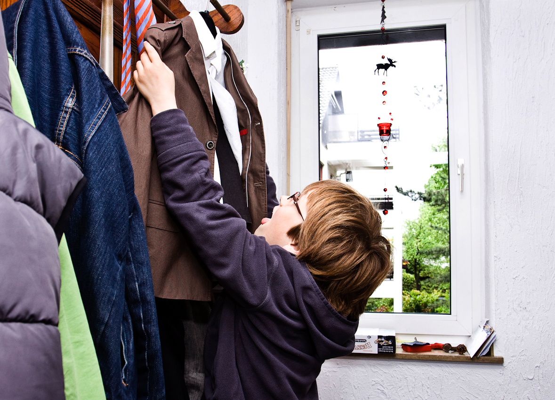 Am Nachmittag des 07.05.2010 im Hausflur der Familie Dicks in Krefeld. Jakob Dicks nimmt seinen Erstkommunionsanzug vom Buegel des Garderobenständers.