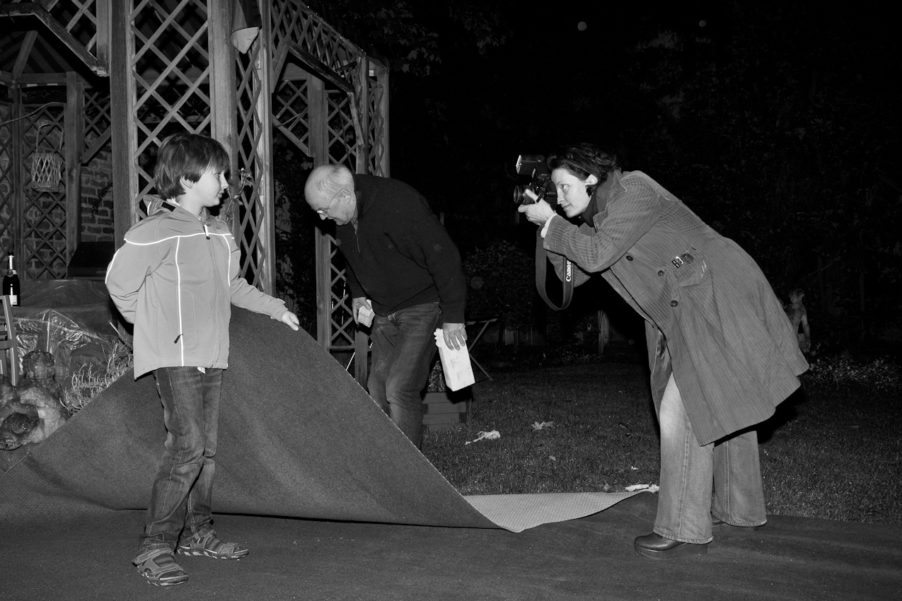 """Fotografin, Yvonne Szallies (rechts), bei der Fotodokumentation zum Thema """"Ein Tag Deutschland"""", am Abend des 07.05.2010 in Krefeld.  In Vorbereitung der Erstkommunionsfeier, hilft Jakob Dicks (links) seinem Vater,  Achim (mitte), beim Ausrollen eines künstlichen Rasens im Garten des Familiengrundstücks."""