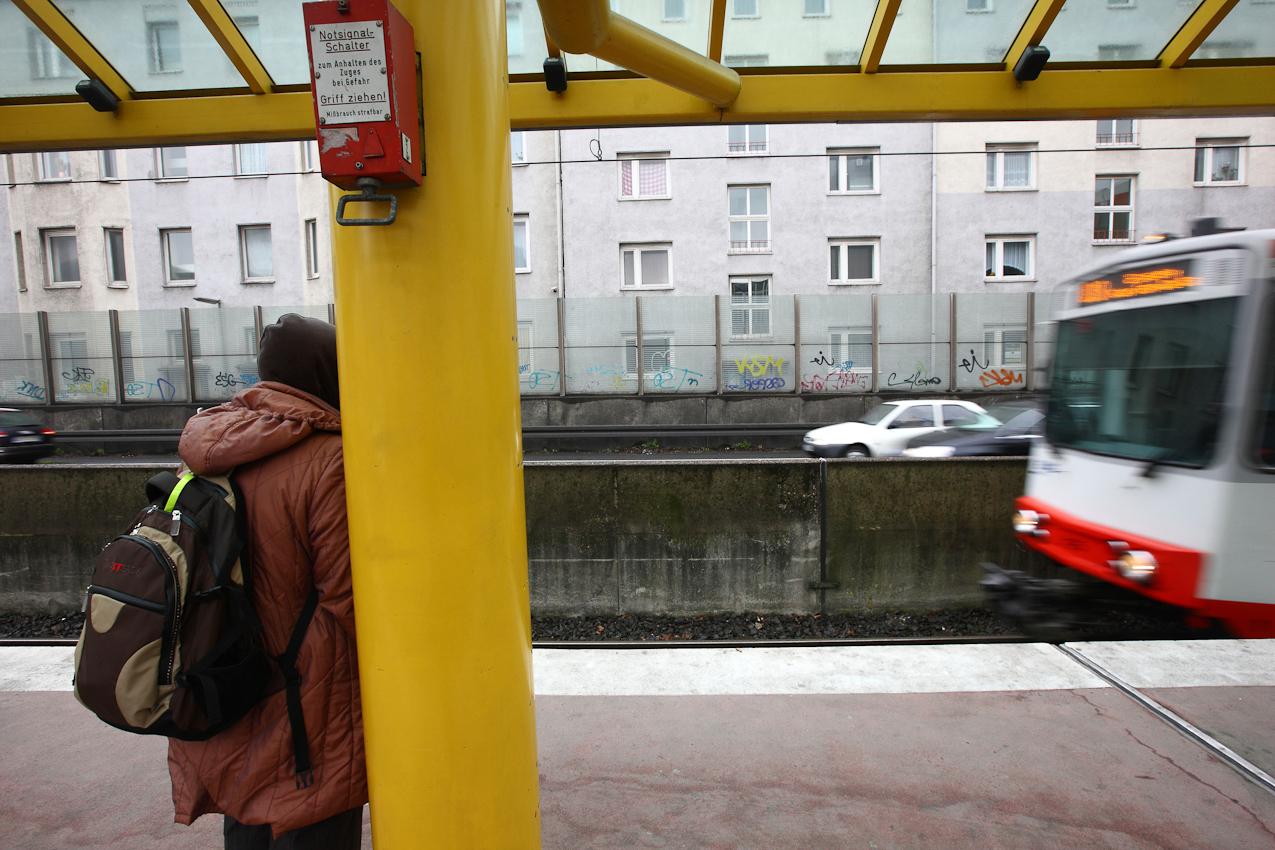 Ein Tag Deutschland, auf der Autobahn A40, Ruhrschnellweg. Fuenf Meter stehen die Wohnhaeuser von der Autobahn entfernt. Zum Laerm der Straße kommt noch das Rattern der Strassenbahnen auf dem Mittelstreifen. Dafuer kommen die Pendler ohne Stau nach Muelheim. Essen, NRW, Deutschland.