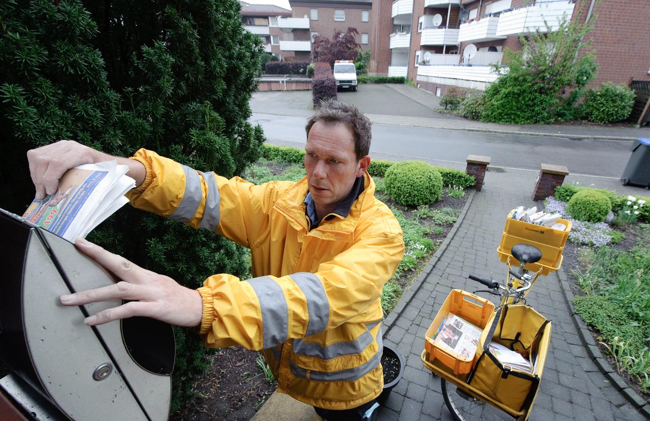 Werne a.d. Lippe, DEU, 07.05.10 - Der Briefzusteller Dirk Leinberger steckt am Freitag, 7. Mai 2010, in Werne an der Lippe bei regnerischem Wetter eine Werbesendung in einen Briefkasten.