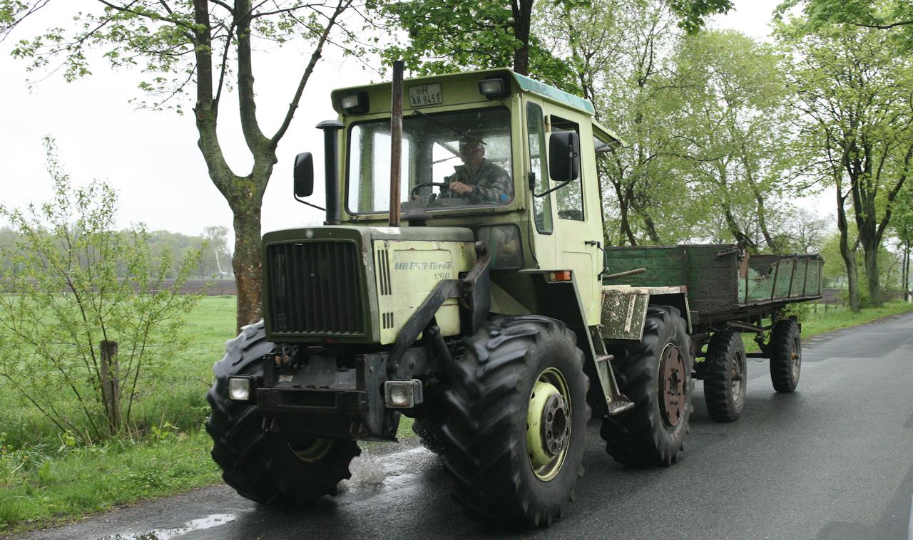 Ein Landwirt ist mit seinem Traktor und einem alten Anhänger unterwegs auf der Straße zwischen Heinhaus und Altenhorst. Die Aufnahme wurde am 07.05.2010 um 10.42 gemacht.