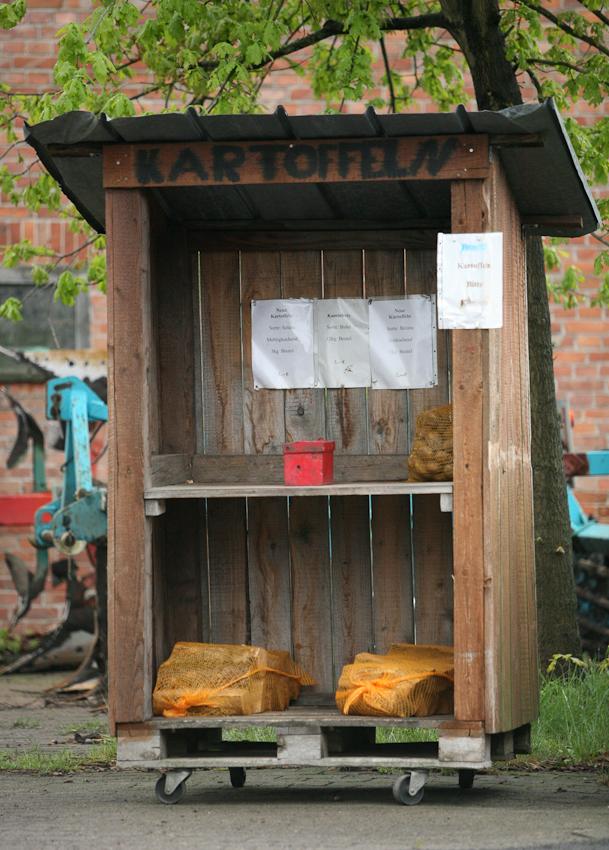 Der Selbstbedienungsstand für Kartoffeln und Kaminholz befindet sich in direkter Nachbarschaft zum Golfpark Heinhaus. Der Landwirt vertraut seinen Kunden. Die rote Box dient als Kasse. Dort wird das Geld für die gekaufte Ware hinterlegt. Die Aufnahme wurde am 07.05.2010 um 12.04 gemacht.