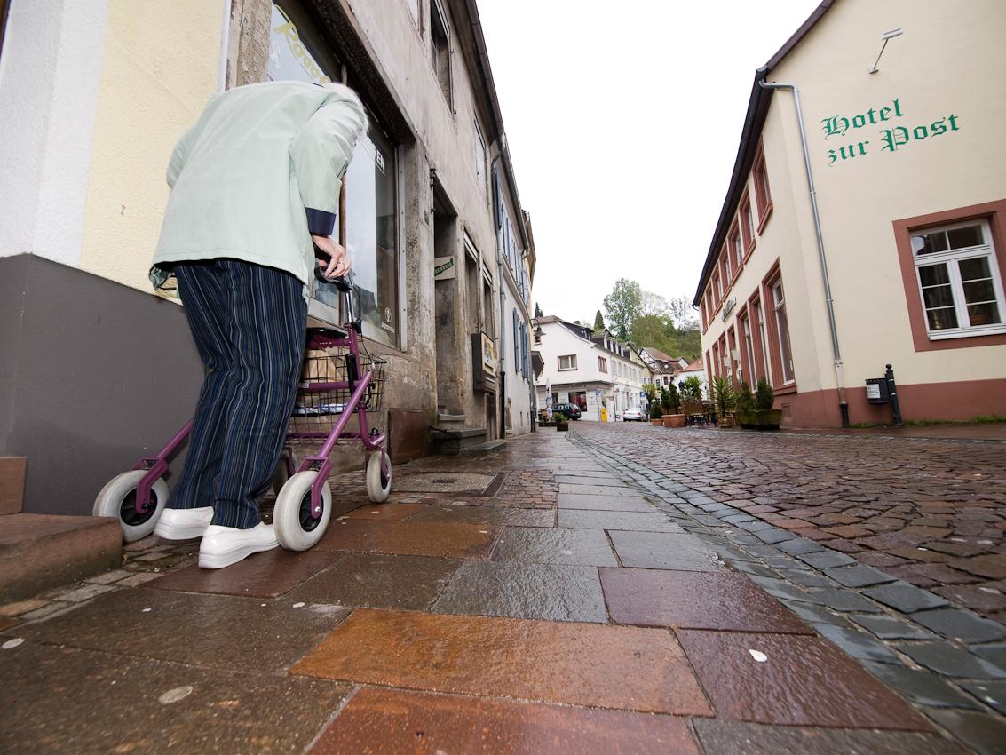 """Vorbei an der """"Alten Post"""", gelangt diese gehbehinderte Frau in die Blieskasteler Innenstadt. Blieskastel ist eine Stadt im Saarpfalz-Kreis im Saarland, Deutschland. Sie liegt etwa 15 km sudwestlich der Kreisstadt Homburg und 25 km ostlich der Landeshauptstadt Saarbrucken."""