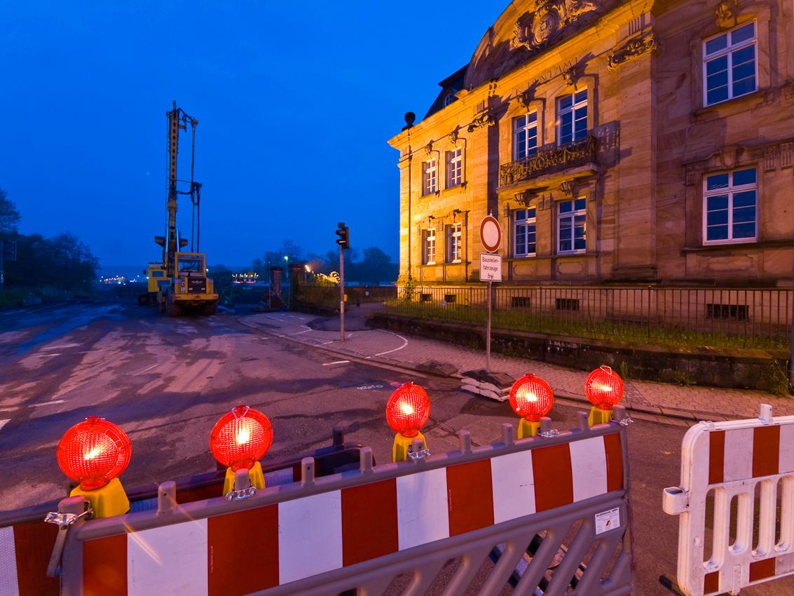 Das ehemalige Rentamt in Blieskastel im Saarland. Der Besucher, der vom Osten uber die Bliesbrucke in die Stadt kommt, sieht auf der linken Seite als erstes einen zweigeschossigen, roten Sandsteinbau mit schiefergedecktem Walmdach. Dieser wurde im Jahre 1904 als Koniglich Bayerisches Rentamt erbaut. Seit 1816 gehorte Blieskastel zum Konigreich Bayern. Im Laufe der Zeit anderte sich mehrfach der Zustandigkeitsbereich der hiesigen Finanzbehorde. 1995 wurde die endgultige Schlie?ung des Finanzamtes in der Zweibrucker-Stra?e 1 beschlossen. An diese Nutzung des Gebaudes erinnert der Schriftzug auf der Nordseite. Die dortige Hauptfassade hat einen Mittelrisalit, einen schmalen Balkon und einen Rundbogengiebel mit dem bayerischen Wappen. Im Obergeschoss der ostlichen Fassade erkennt der Betrachter einen Erker mit aufschwingendem Rundbogengiebel und einem Medaillon mit behelmtem Mannerkopf. Alle Pilaster und Eckpilaster sind uber dem Dachgesims von Vasen bekront. 1975 schien das Schicksal dieses neobarocken Gebaudes besiegelt. Im Zuge einer Stra?enbauma?nahme sollte es abgerissen werden. Zahlreiche Initiativen aus der Region setzten sich fur den Erhalt des geschichtstrachtigen und vielleicht schonsten Finanzgebaudes im Saarland ein und verhinderten schlie?lich den Abriss. 1978 wurde das Gebaude unter Denkmalschutz gestellt und restauriert. Seit 1996 ist darin ein Teil der Stadtverwaltung untergebracht. Derzeit wird eine Brucke und die Verlegung der Landstra?e in unmittelbarer Nahe dieses Rentamtes gebaut. Der erste Bauabschnitt umfasst den Bau der innerortlichen Umfahrung auf einer Strecke von 765 Metern, den Bau der Behelfsumfahrung uber die Blies -einschlie?lich Errichtung einer Behelfsbrucke- sowie den Neubau einer 80 Meter langen Flutbrucke. Die Baukosten betragen insgesamt 11 Millionen Euro.